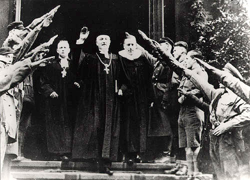 """National Bishop Friedrich Coch giving a Hitler greeting in Dresden, 10 December 1933   Dresden pastor Friedrich Coch is one of the leading men of the """"German Christians"""" in Saxony. The NSDAP's Gau consultant for church matters since 1932, he is elected to the office of state bishop by the """"Brown Synod"""" in August 1933.  (Source:  Gedenkstätte Deutscher Widerstand )"""