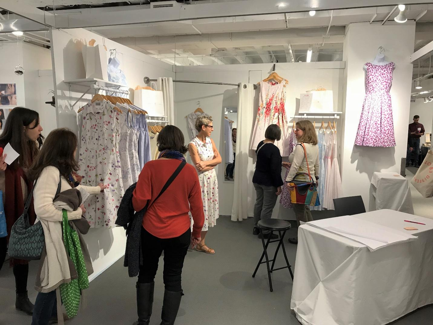 Anikka Becker in her booth at a show discussing her everyday dresses with customers.