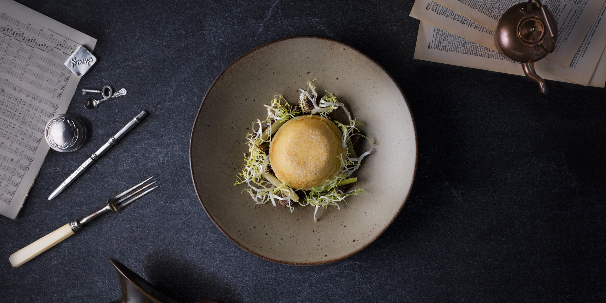 The Grahamston I Twice Baked Isle of Mull Cheddar Souffle served with braised celery, warm grape chutney, frizzy endive and roasted chestnuts