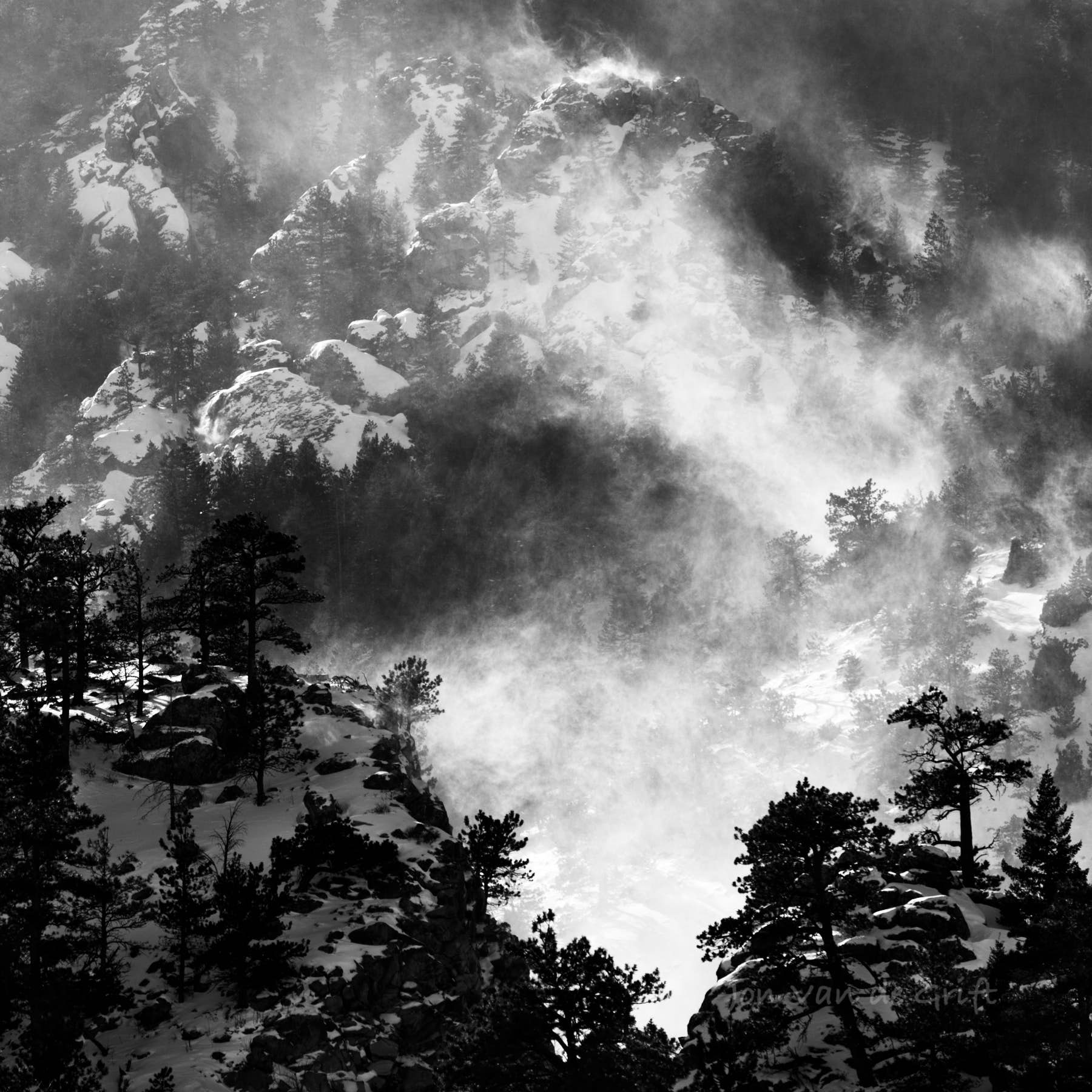 Blowing snow across a steep mountain during winter, captured in black and white.