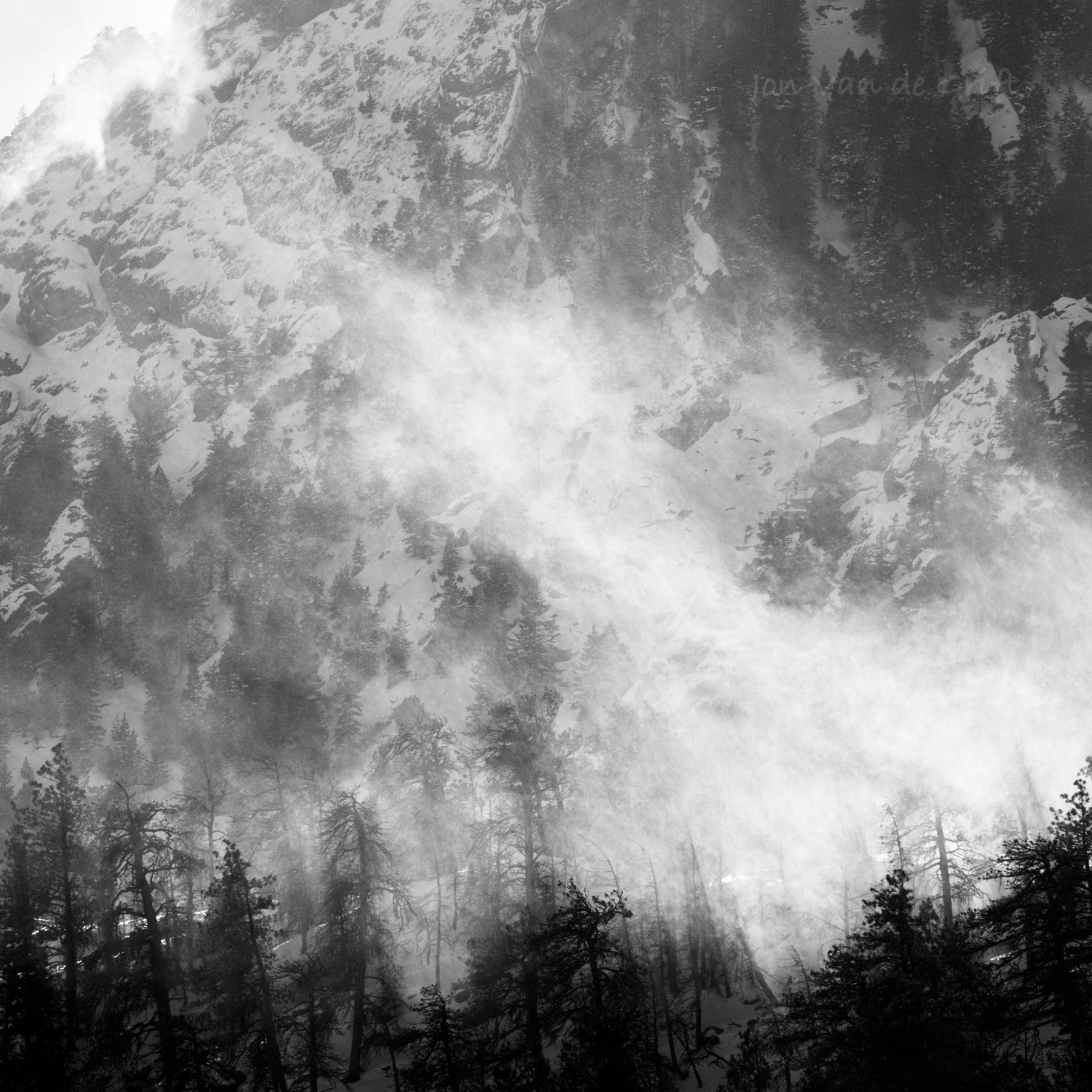 Black and white photograph of a ground blizzard in a mountain range during winter.