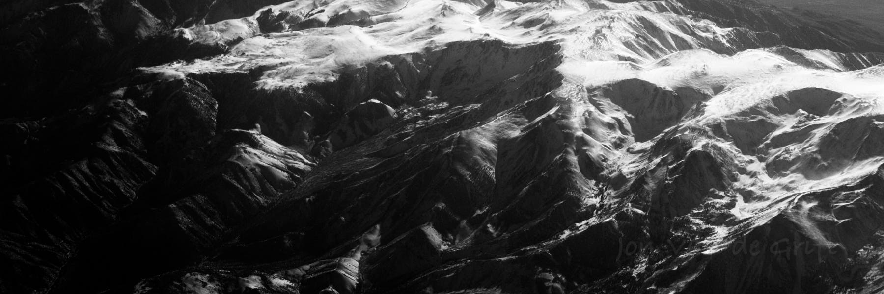 Black and white aerial photograph of snow pack on mountains in sunlight and shadow.