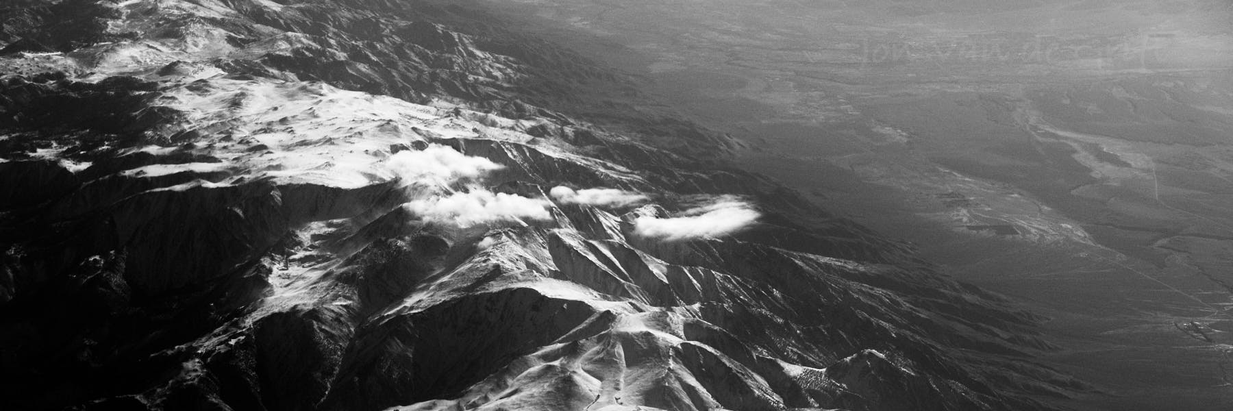 Black and white aerial photograph of clouds and snow along a mountain ridge.