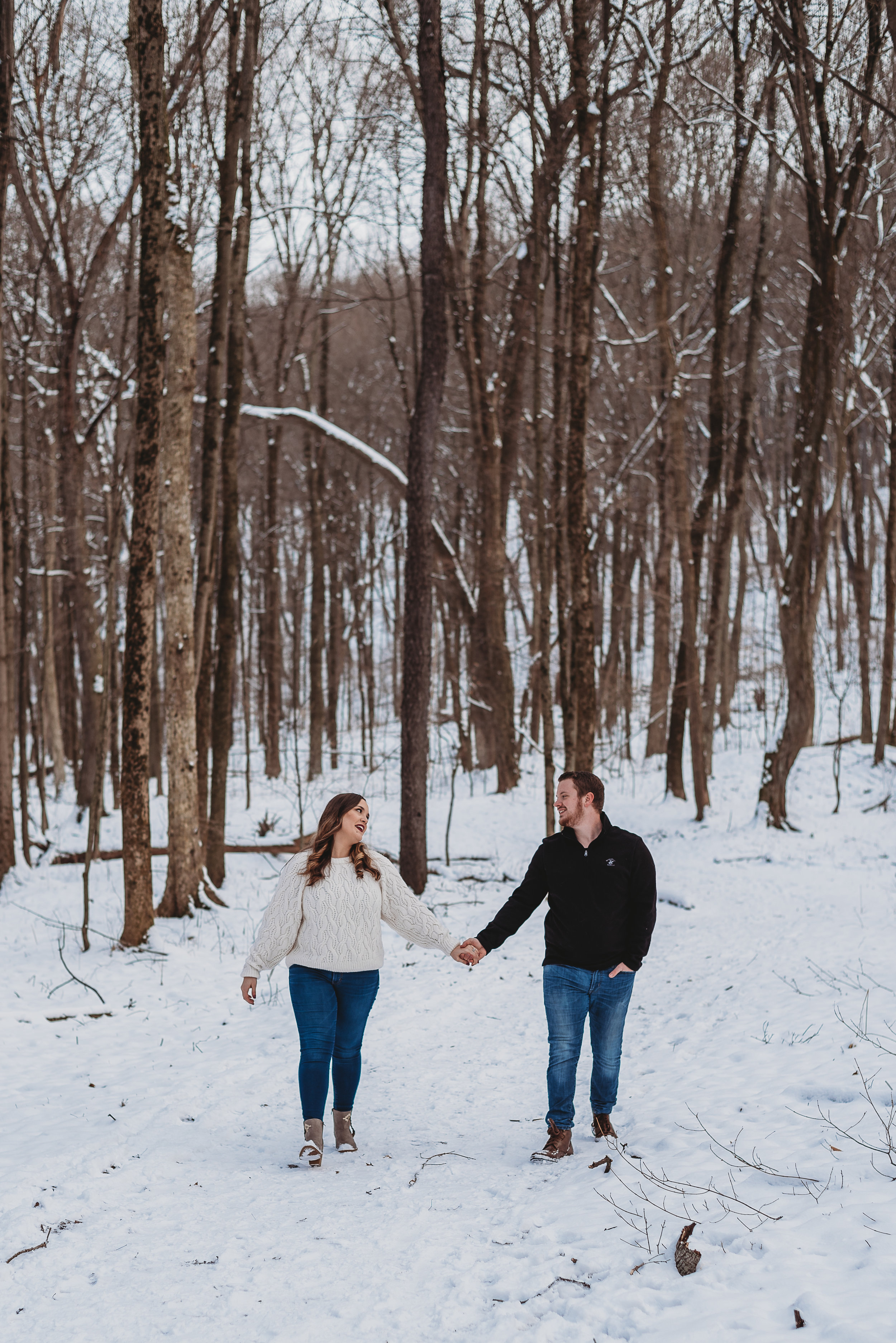 engaged couple smiling in snow