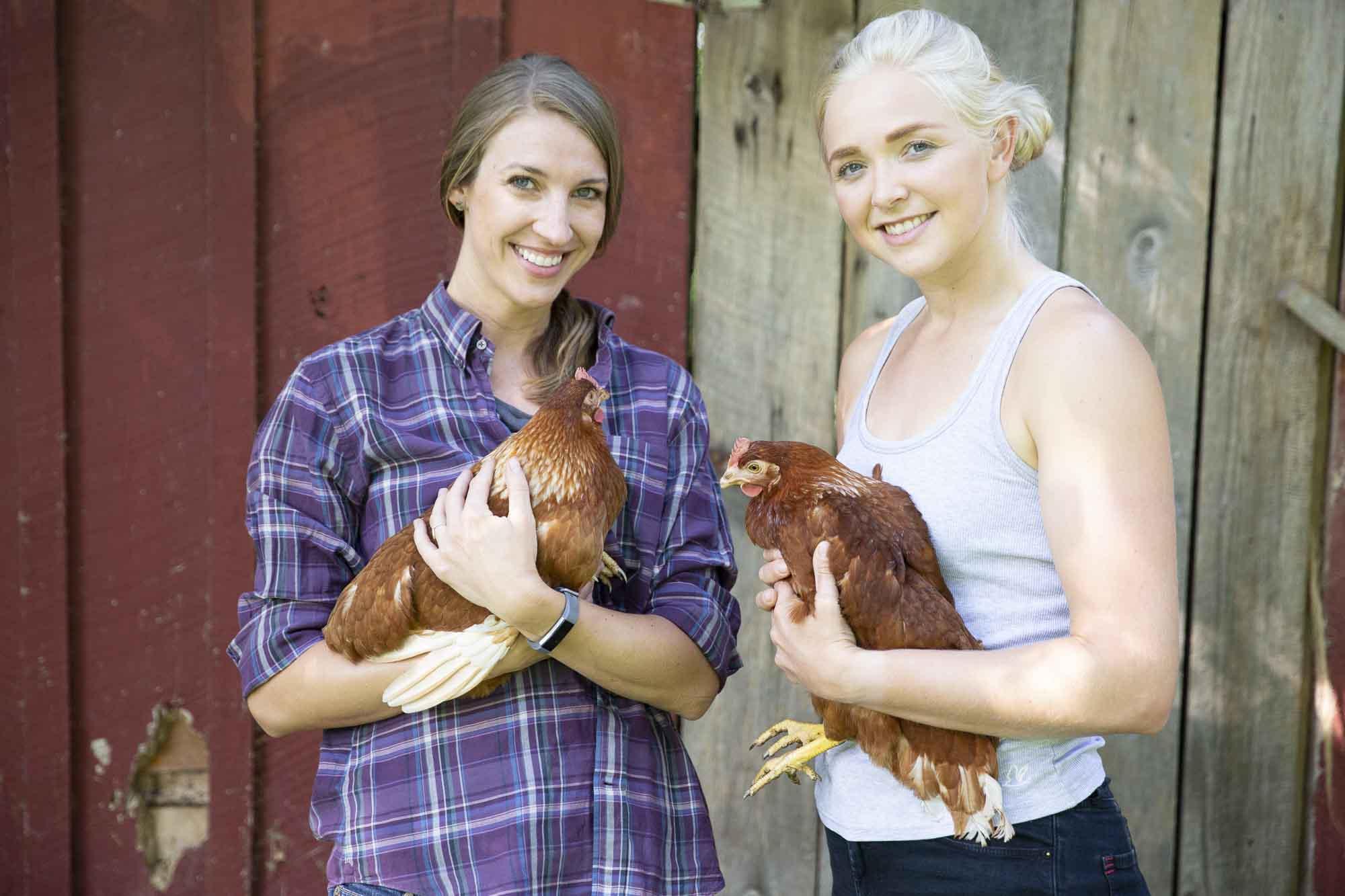 Sarah & Pam hold chickens, the cuddliest feathered farm animal