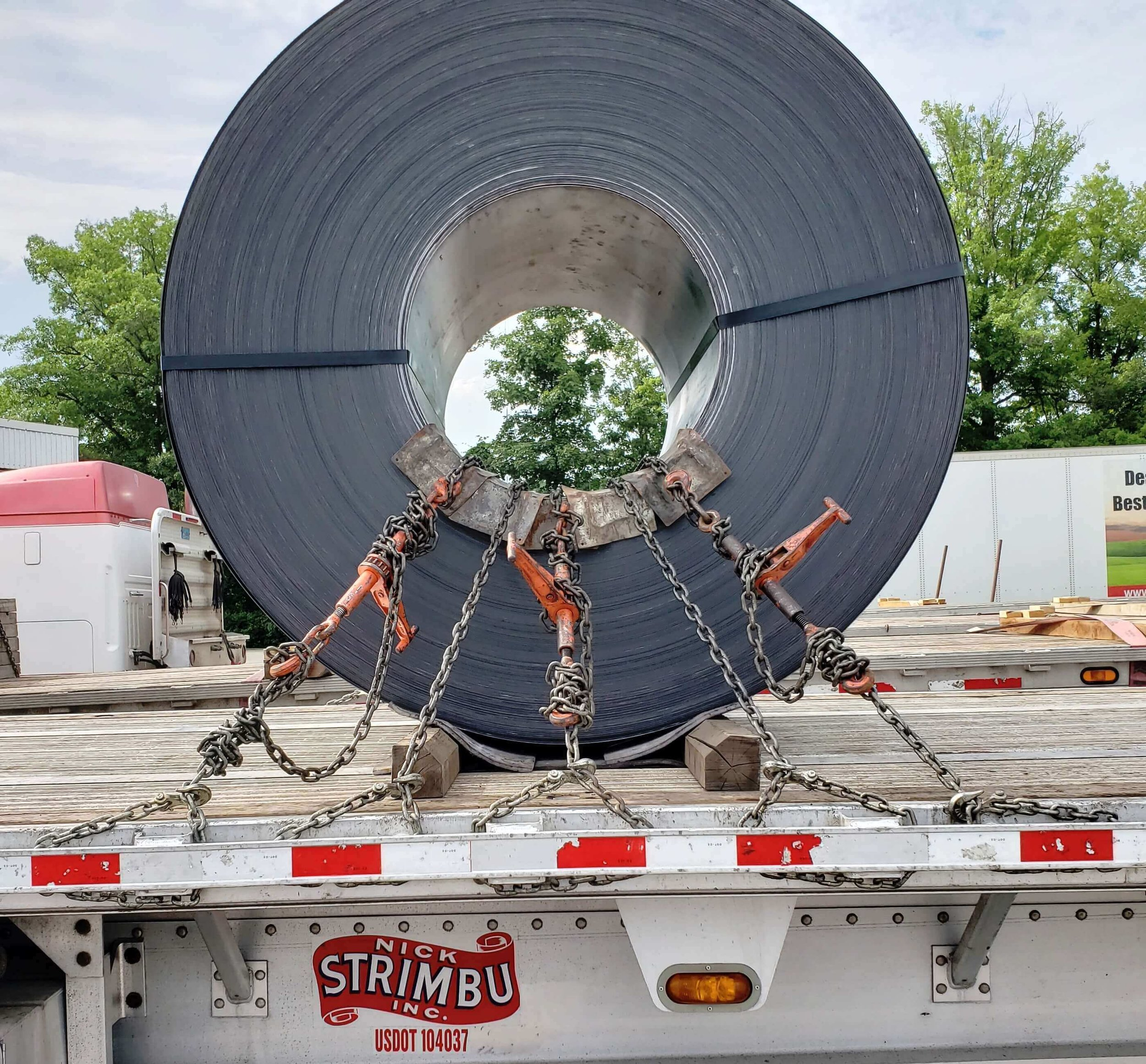 C-5:  2 chains pulling forward, 2 chains pulling rearward, 1 chain pulling straight down. Observe the rating of the trailer securement point. It is against regulations to cross chains in eye to the side coils