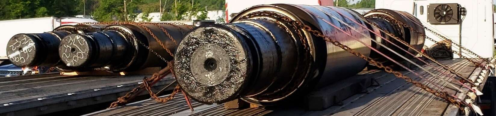H-5:  The load on the left is belly loaded side by side. The weight is concentrated in the center of the trailer. 6 tie downs are securing both rolls. The ends are choked, pulling them together. The identical load on the right is loaded end to end. The weight is spread out over the length of the trailer. 6 tie downs are securing each roll. The ends are choked, mechanically securing the rolls from sliding.