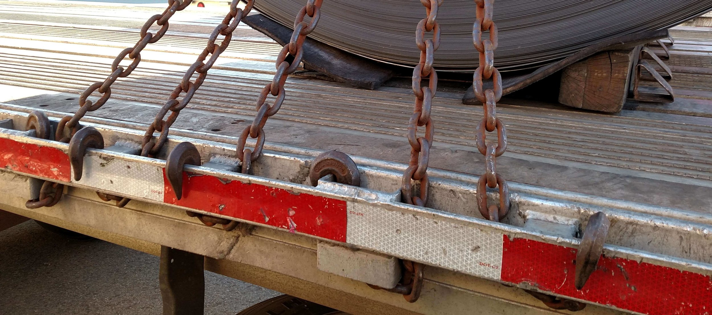 J-3:  Chains are hooked on rub-rail, and not taking advantage of the stronger spools and stake pockets. The hooks protrude outside rub-rail.