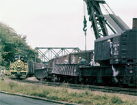 JANUARY - Whoops! It's the mid-1950s, and steam crane X50009 and the wreck crew are there to clean up a minor derailment in Fremont, Ohio, while Geep 453 tiptoes past. - Bob Lorenz photo, Thos Gascoigne collection
