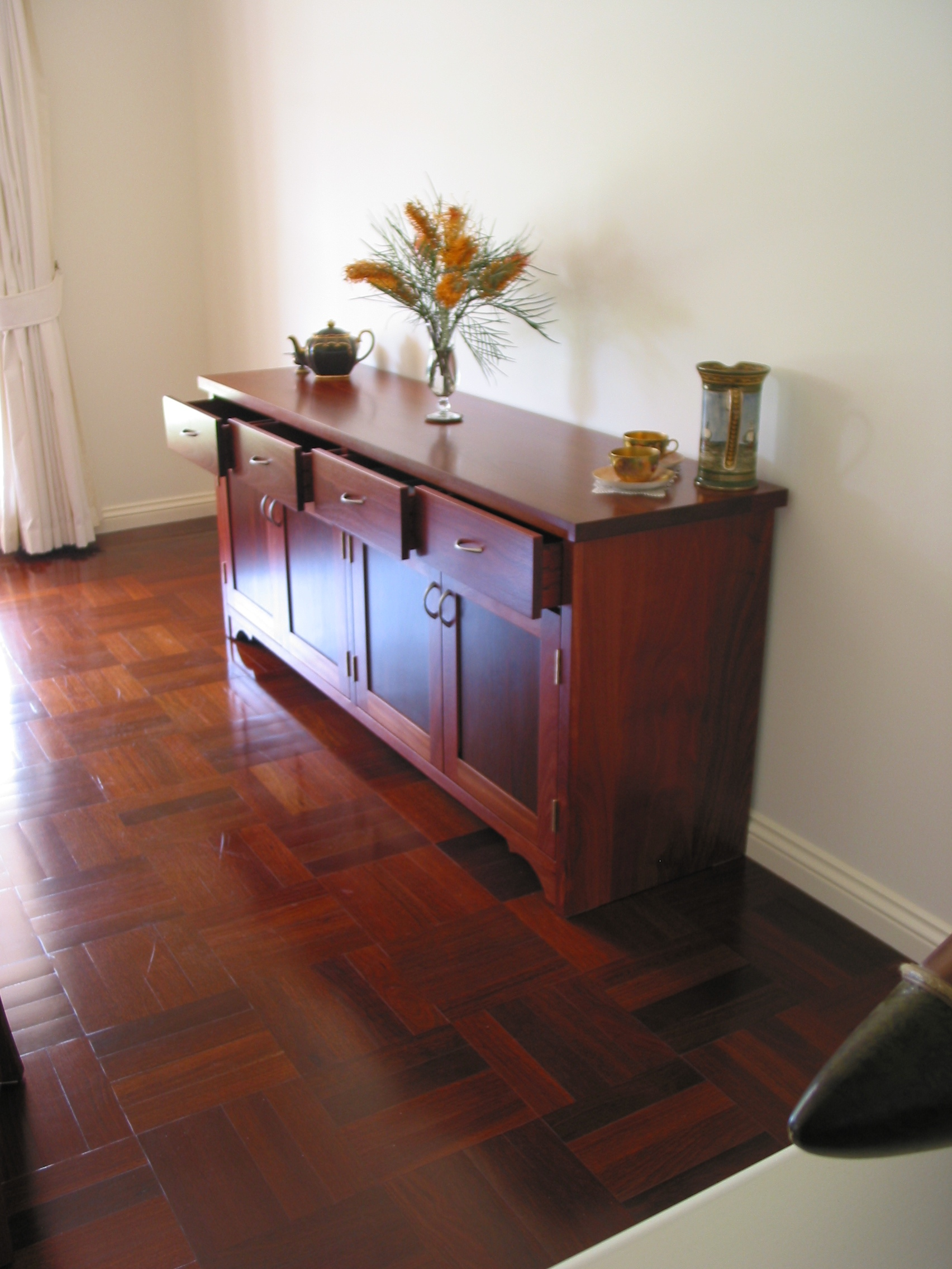 Using the richness of Jarrah this sideboard featuring ample storage is a wonderful addition to this dining room .