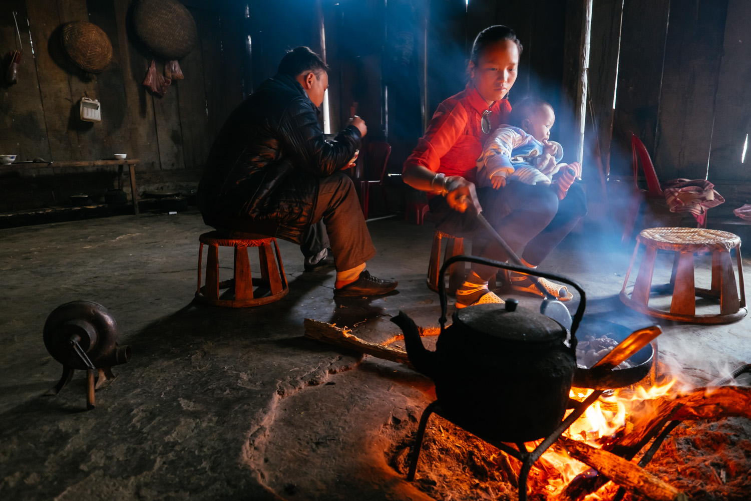A young mom form the Hmong tribe who works as a tour guide in Sa Pa, Vietnam, cooks dinner at her home after a full day of trekking through the mountains.