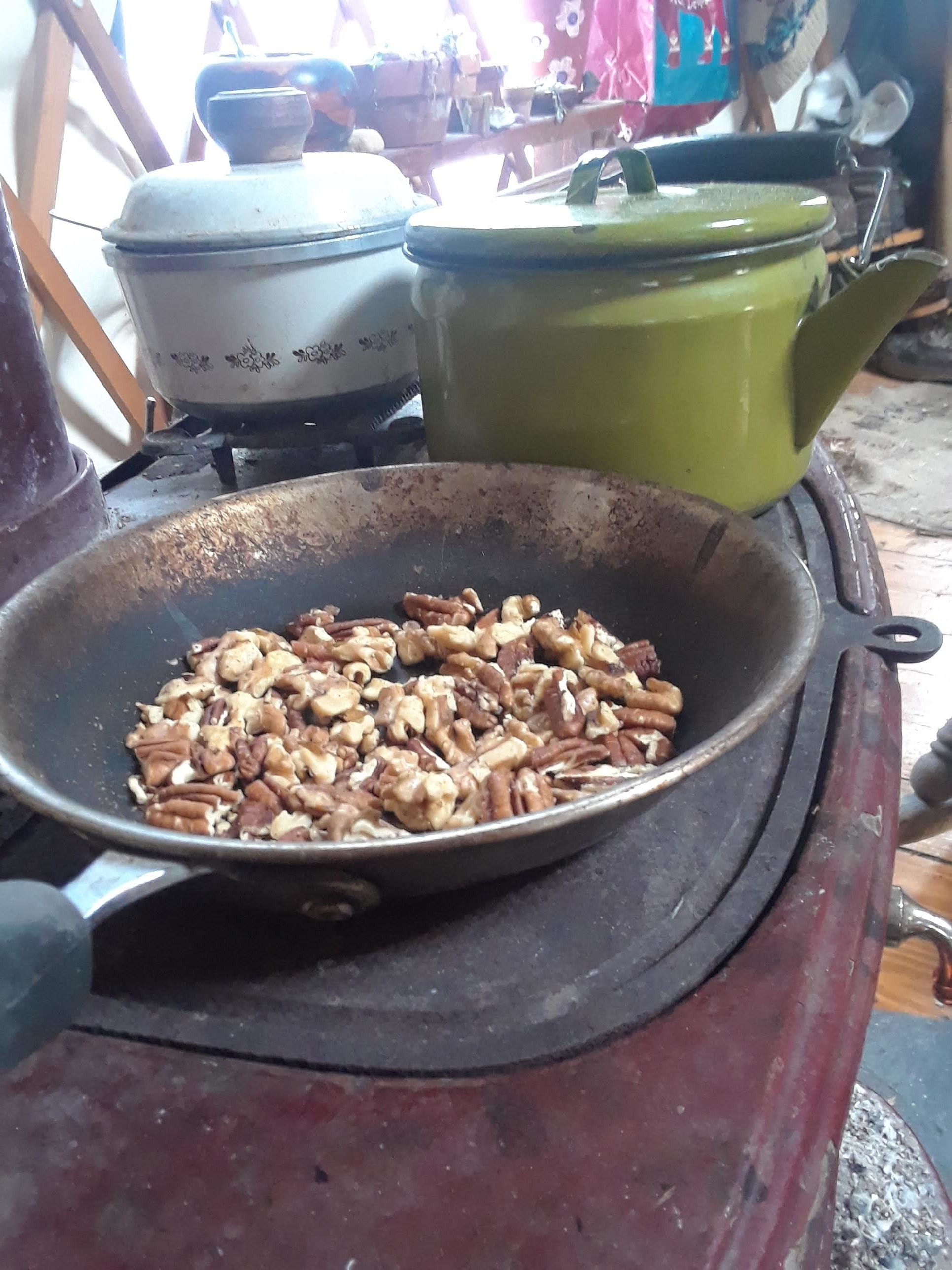 A principle of permaculture—stacking functions. Warming the yurt, keeping breakfast warm, boiling water for tea, and toasting nuts (and cats, not pictured) all at once! This is our designated nut pan, the oils have blackened but it doesn't affect the taste.