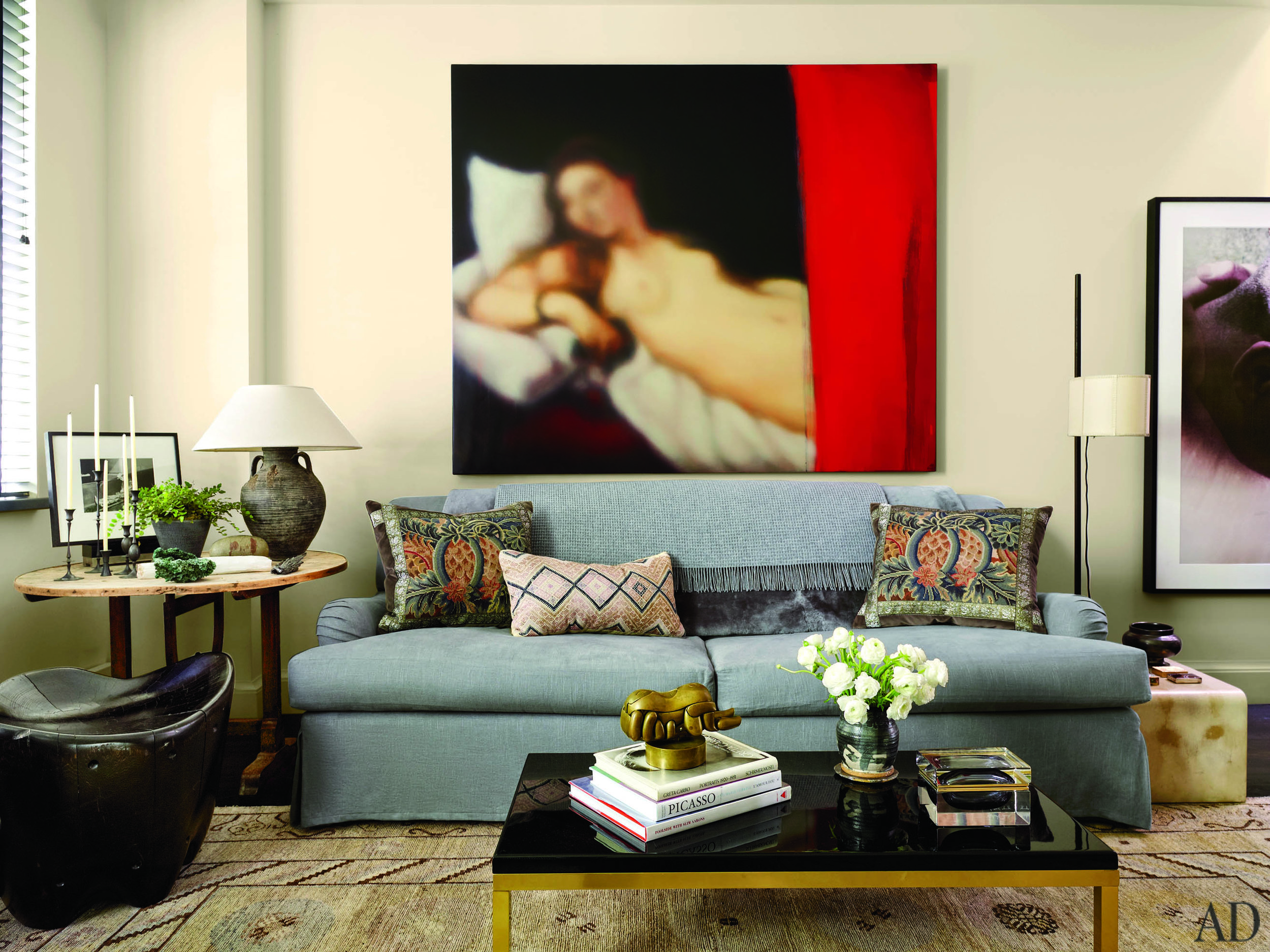 A Jeff Muhs painting hangs above a Bridgewater sofa in the living room; the floor lamp is by  Roman Thomas .