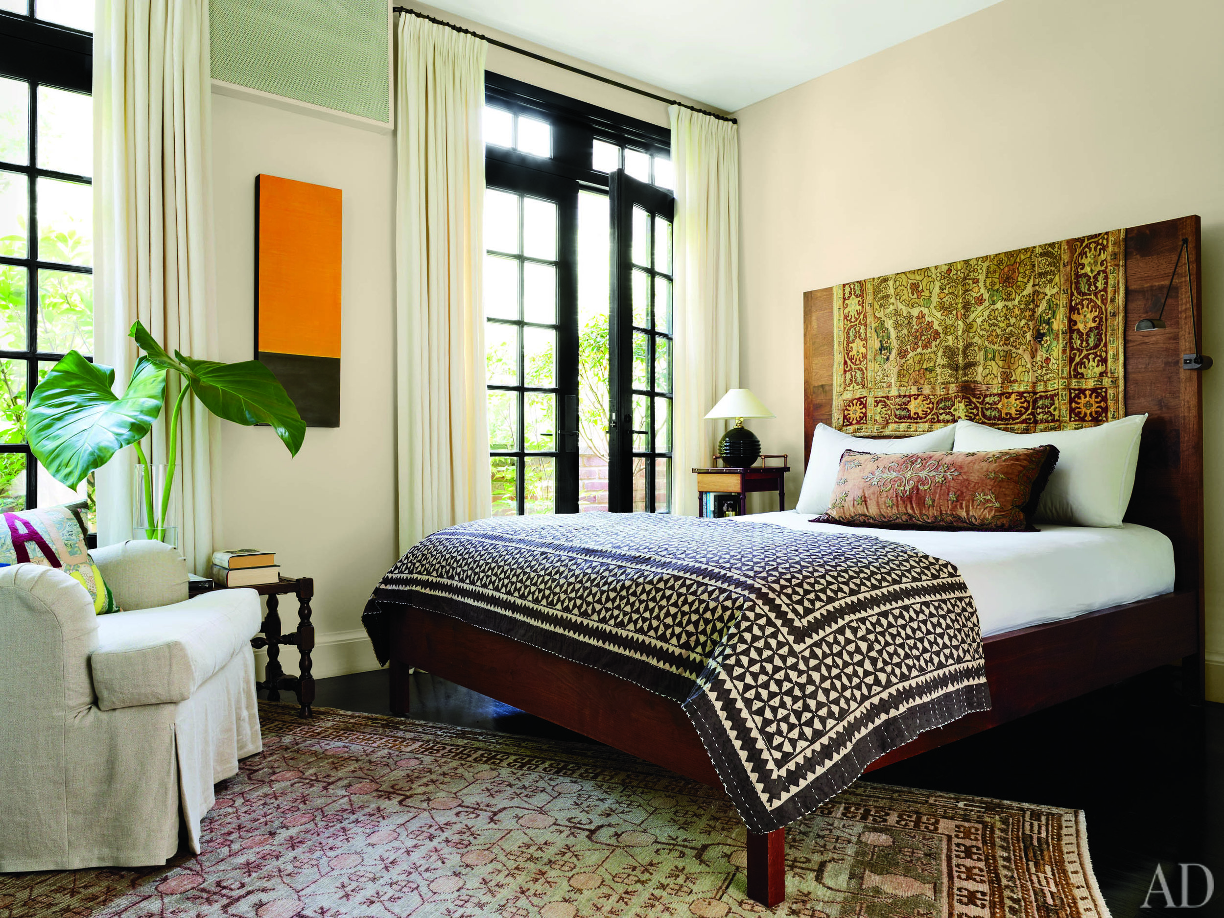 A 19th-century Turkish textile is draped over the headboard of a  BDDW  bed in the master suite.