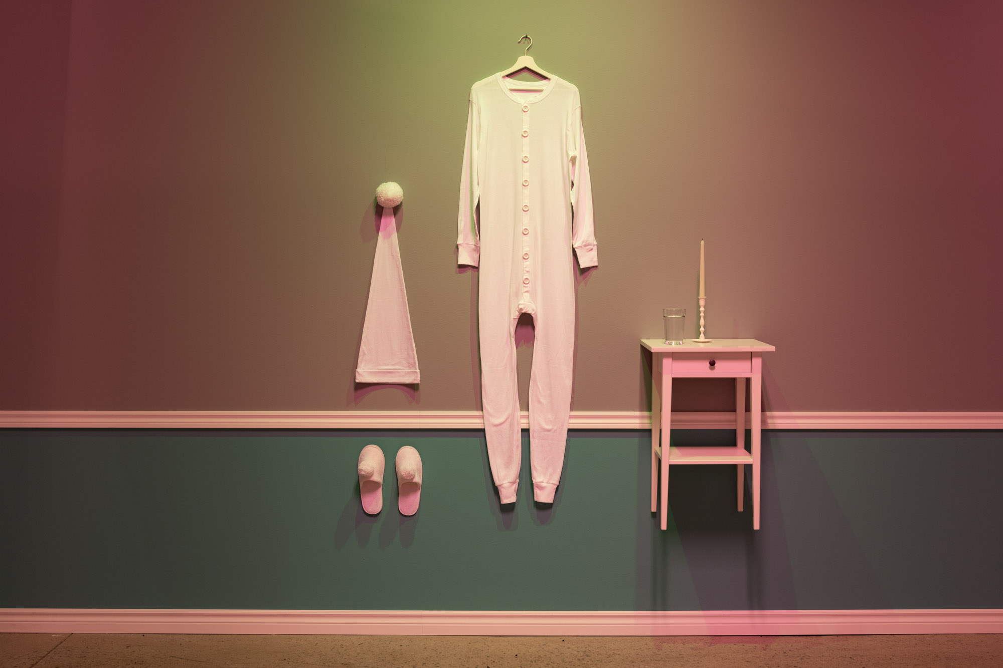 "Ritual , 2019, Union suit, sleeping cap, slippers, night stand, glass of water, burning candle, hanger, molding, acrylic, nail, 88"" x 64"" x 14"""