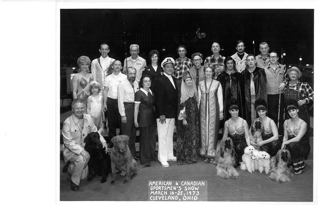 Company founder Sam Stryffeler, (center, between the exotic ladies), poses with performers of the 1973 American and Canadian Sportsman Show held in Cleveland, Ohio.