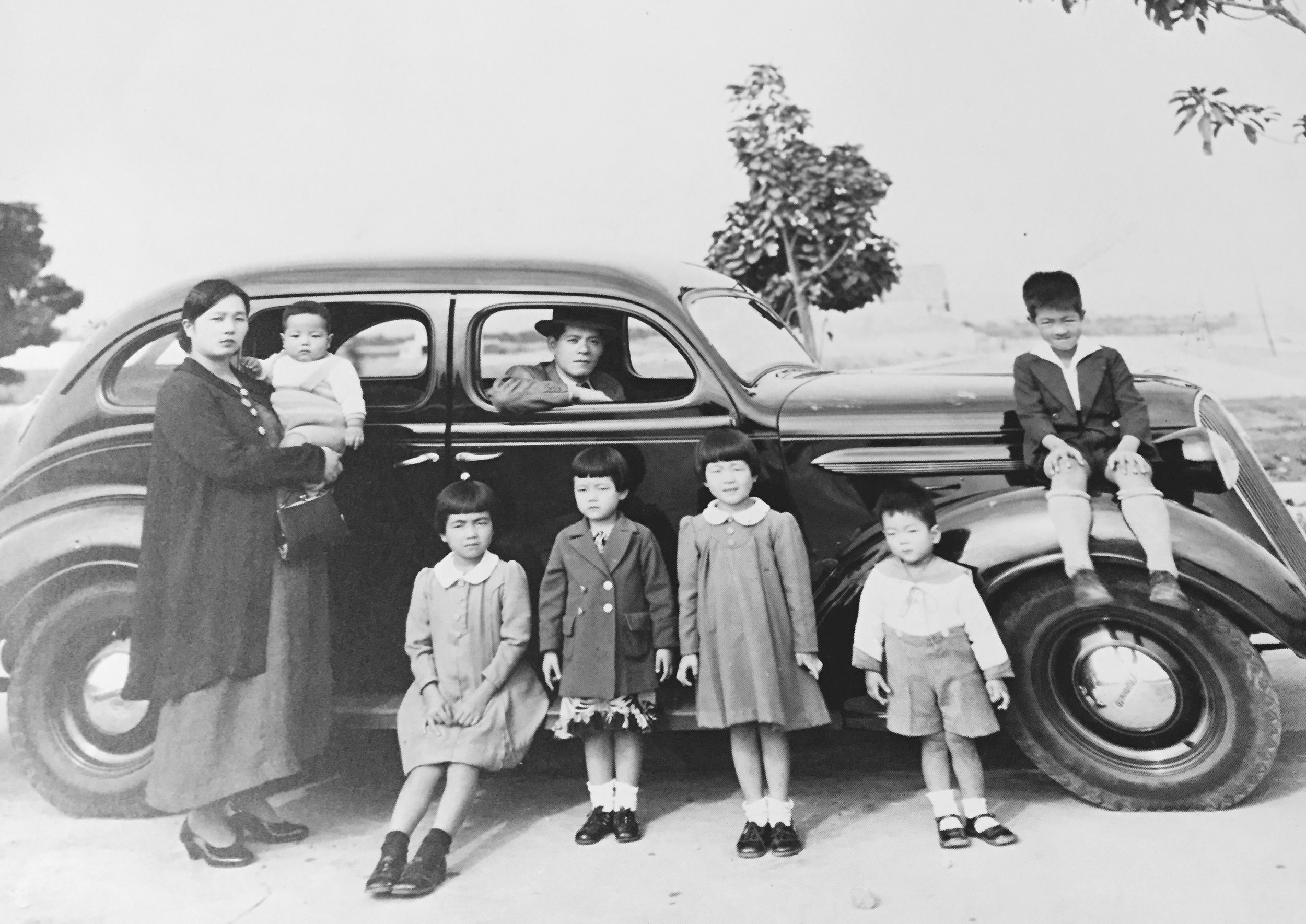 The Shibayama family at a park in Peru. From left to right: Tatsue (mother), Takeshi, Fusako, Akiko, Kikue, Kenichi, Art, and Yuzo (father) in front seat of car.
