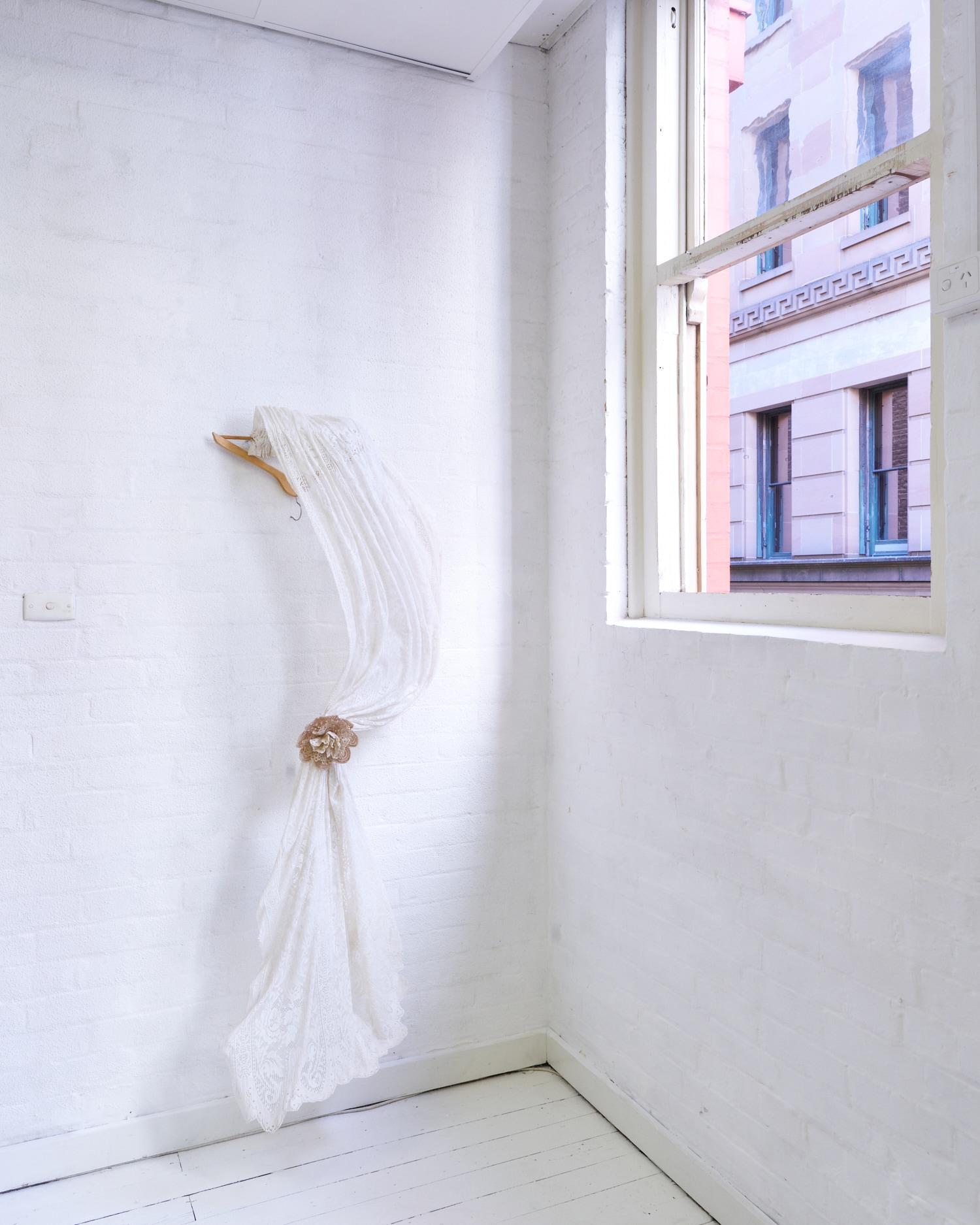 Tamara Baille,    Roman blind,  2019.   Lace curtain doilies, sugar, coat hanger.