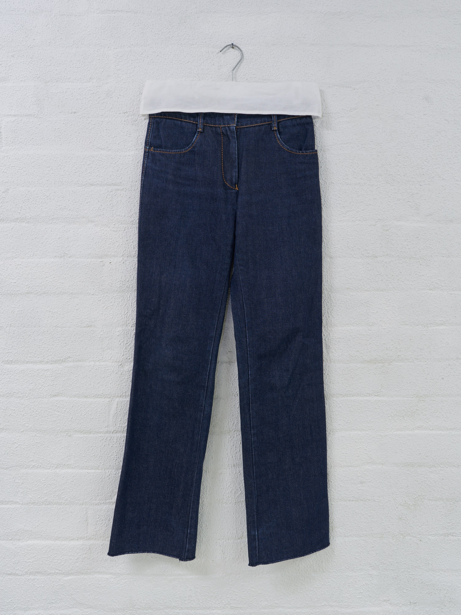 Filter Store,  Maison Martin Margiela fabric covered clip hanger,  mid 2000s. Metal, plastic, cotton. Pictured here hanging some jeans.