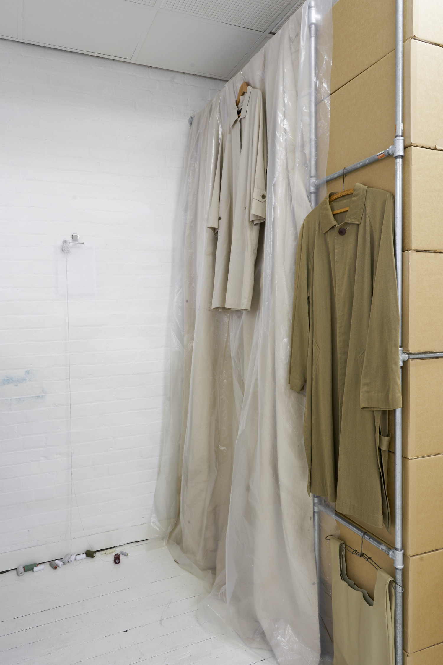 left: Pony Horseman,  Maintenance , 2019. Found objects: PVC binder sheets, assorted threads (cotton and polyester), metal fixtures.  top: Clare Matthews,  Purchased hanger attached to garment , date unknown. Wood and metal.  bottom: Simon Blight,  Found hanger , date unknown. Metal.