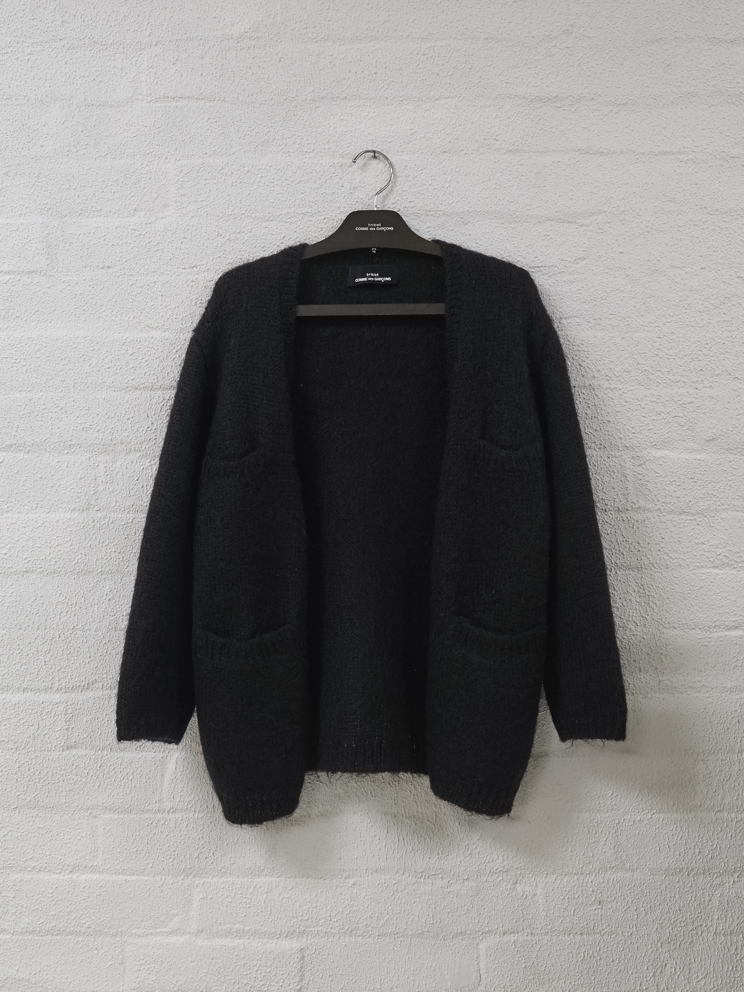 Filter Store,  Tricot Comme des Garcons brown wooden hanger,  c.1980s with a Comme wool cardigan. This hanger was nestled on the racks for 'hangers', here its hanging on the wall.