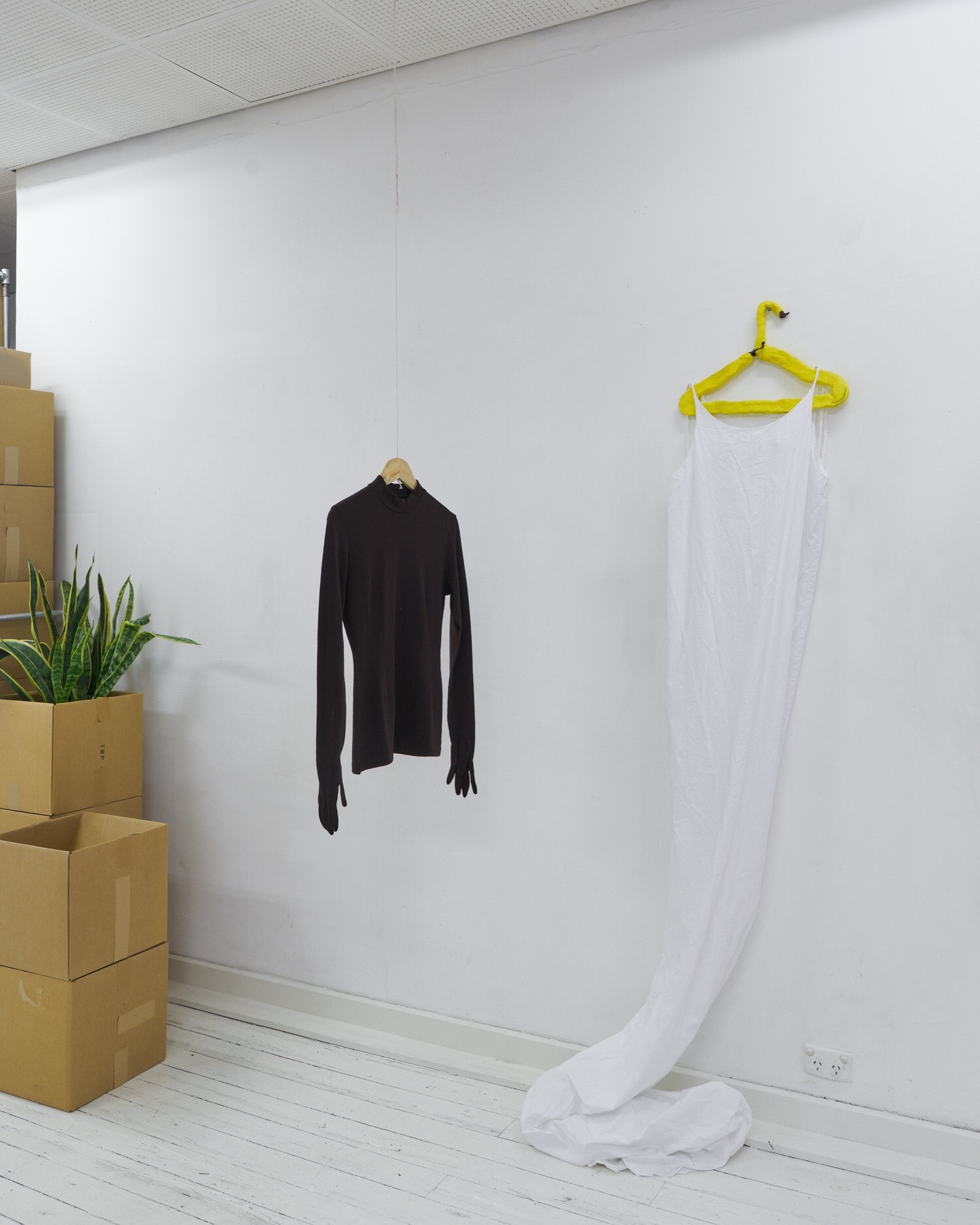 right: Tara Rowhani-Farid,    Oh no no no , 2019.   Air-drying clay, coat hanger, acrylic paint.