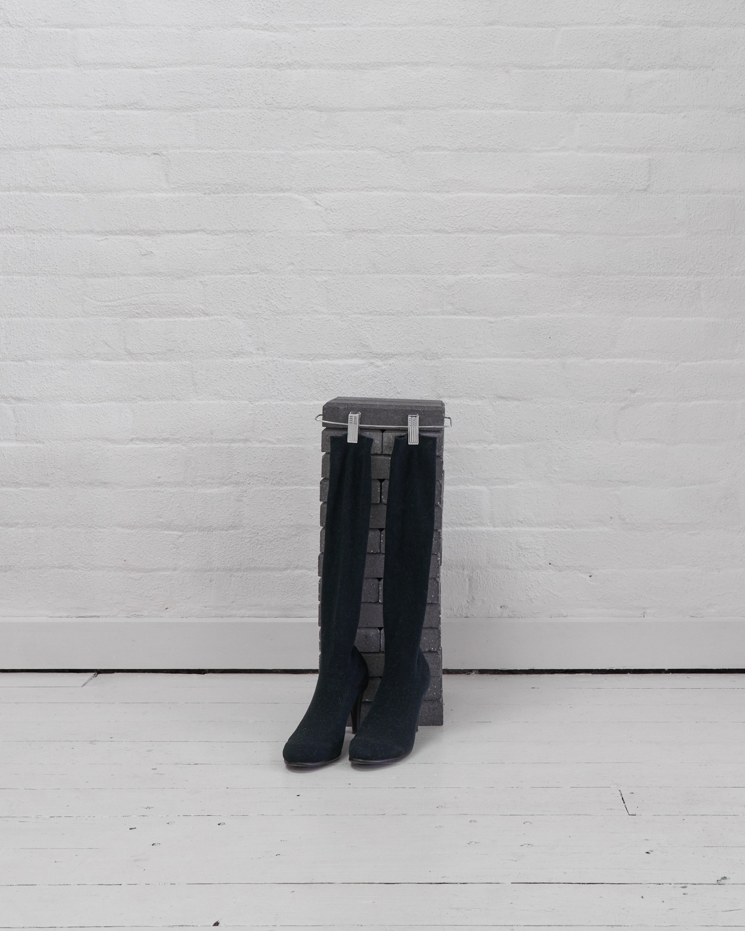 Eleanor Amor,  Shoe and sock stand,  2019. Brick and metal.