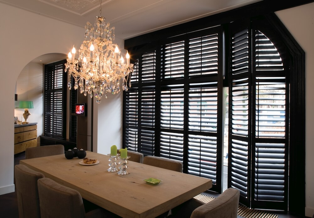 Specialty Shape Shutters    Black wood bi-fold shutters from Norman Window Fashions with angled corners.