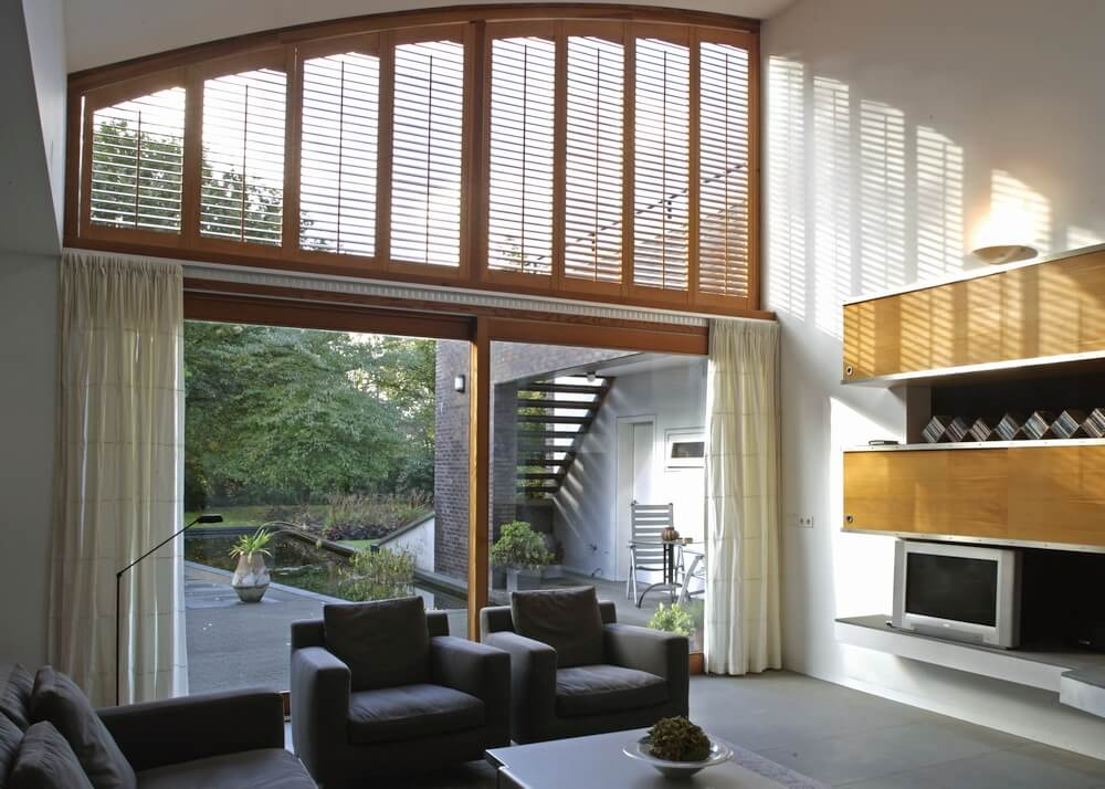Specialty Shaped Shutters    Motorized wood stained shutters for this angle top window above a sliding glass door.