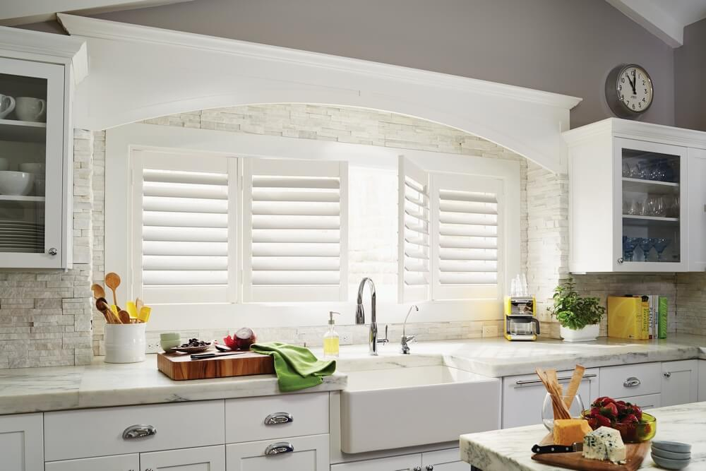Kitchen Plantation Shutters    Bright white bi-fold faux wood shutters on a wide kitchen window with no tilt bar.