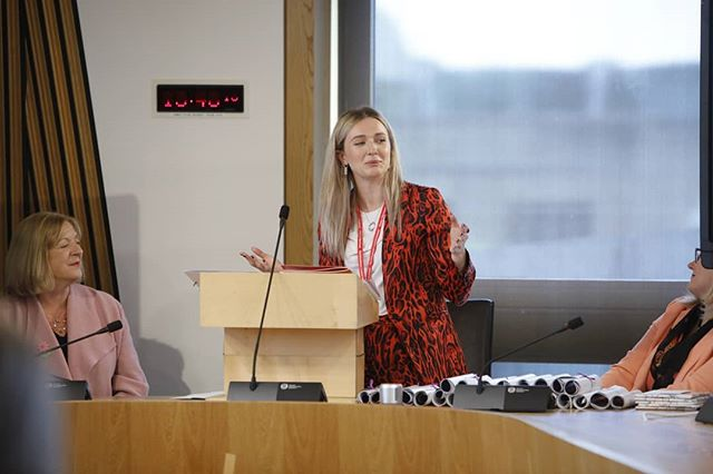 [image of Beth in a red leopard suit speaking at parliament with a black microphone on a brown wooden box. To her left is Linda Fabiani MSP in a pink jacket and to her right is Christina McKelvie MSP] Today @bacloughton is doing a takeover! The programmes intern at @scotwomenrise & @youngwomenscot, Beth will be talking about her journey into politics, gentrification, and a whole host of other feministing things! . . #feminism #womensrights #activism #politics #fmqs  Pic by @scotparl