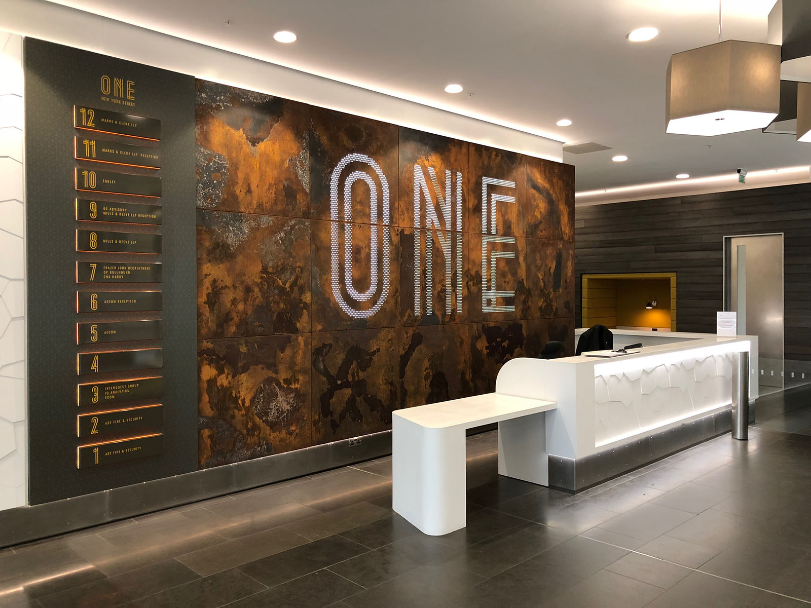 Feature branded light box sign and metal patina in reception