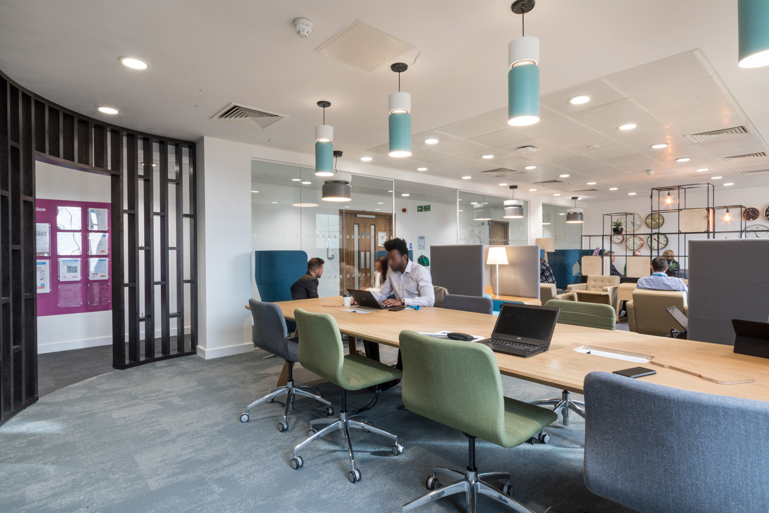 Office interior with green and blue chairs, breakout booths and Spacestor palisades grid