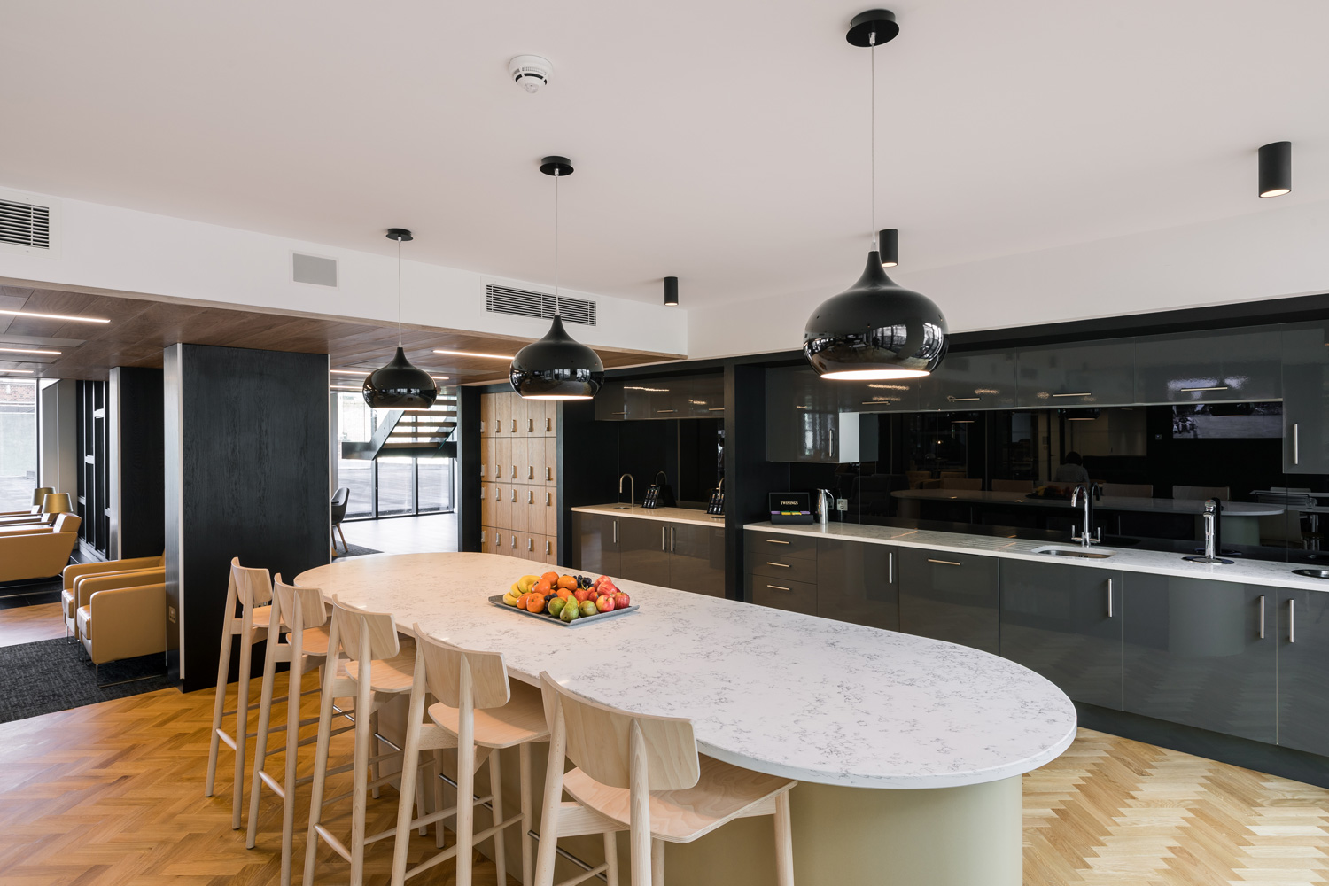 Dark grey office kitchen with marble table top and breakfast bar
