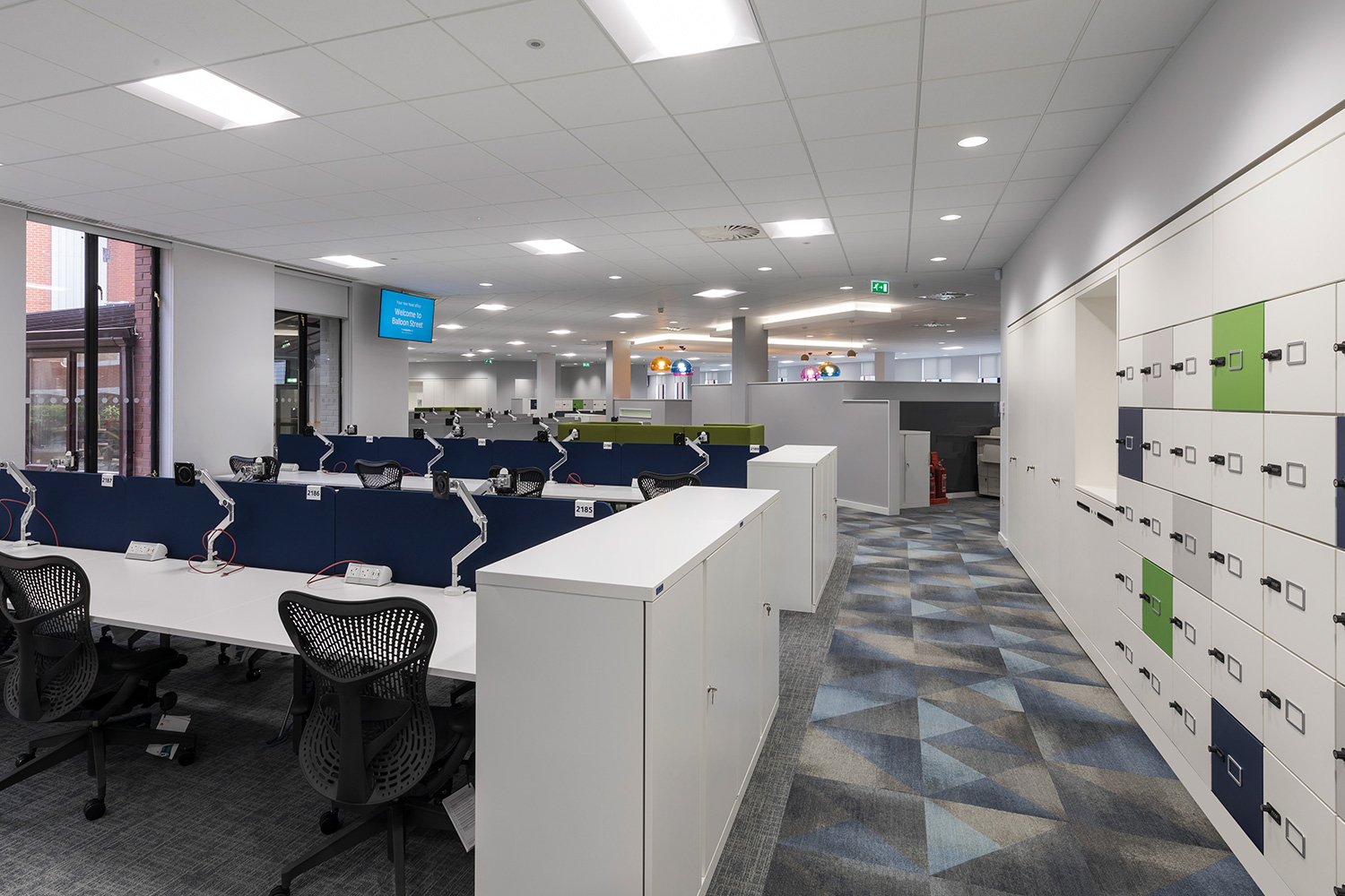 Office desks with blue and green lockers