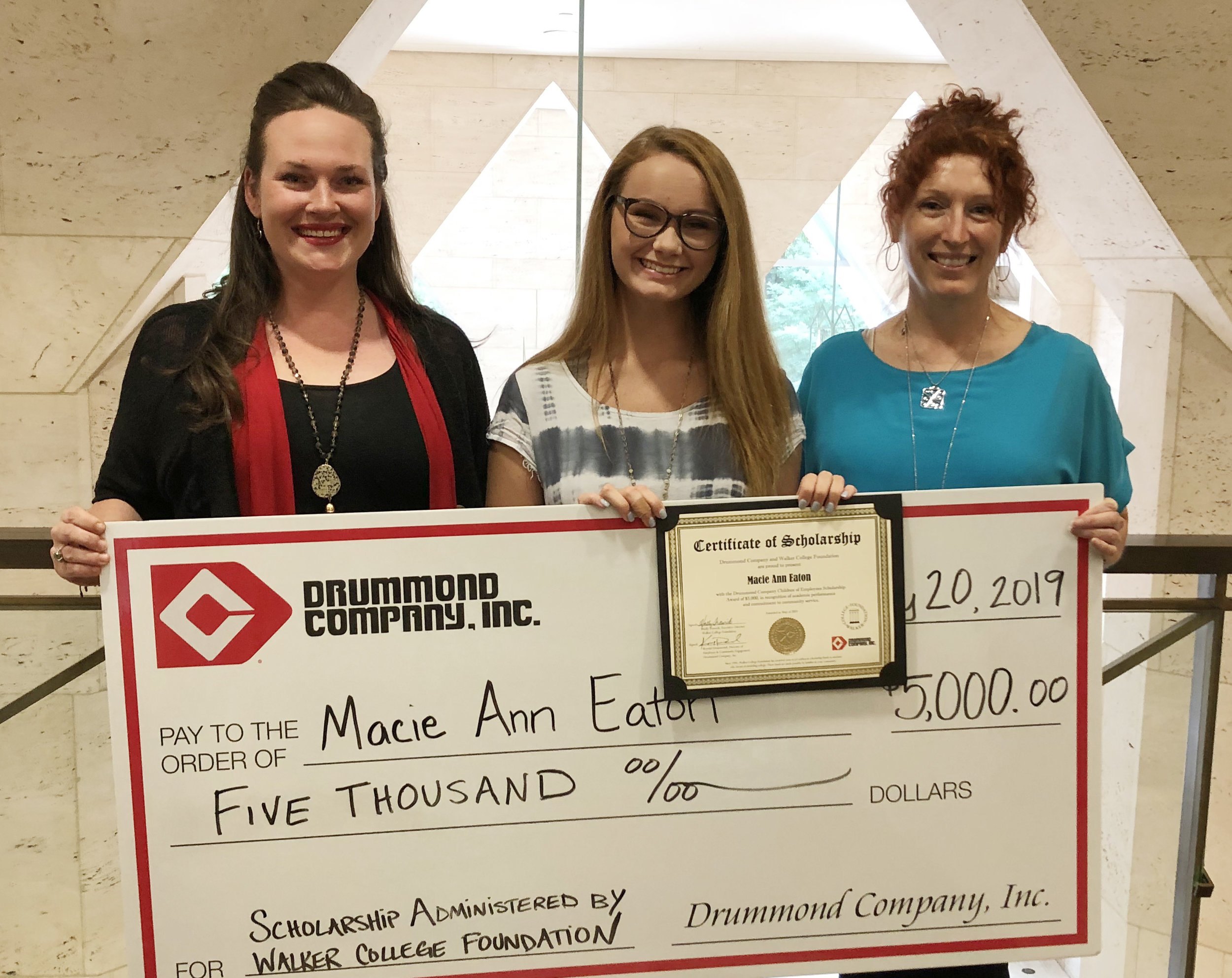 Macie Ann Eaton (ctr) is awarded the Drummond Company scholarship by Krystal and Holly.