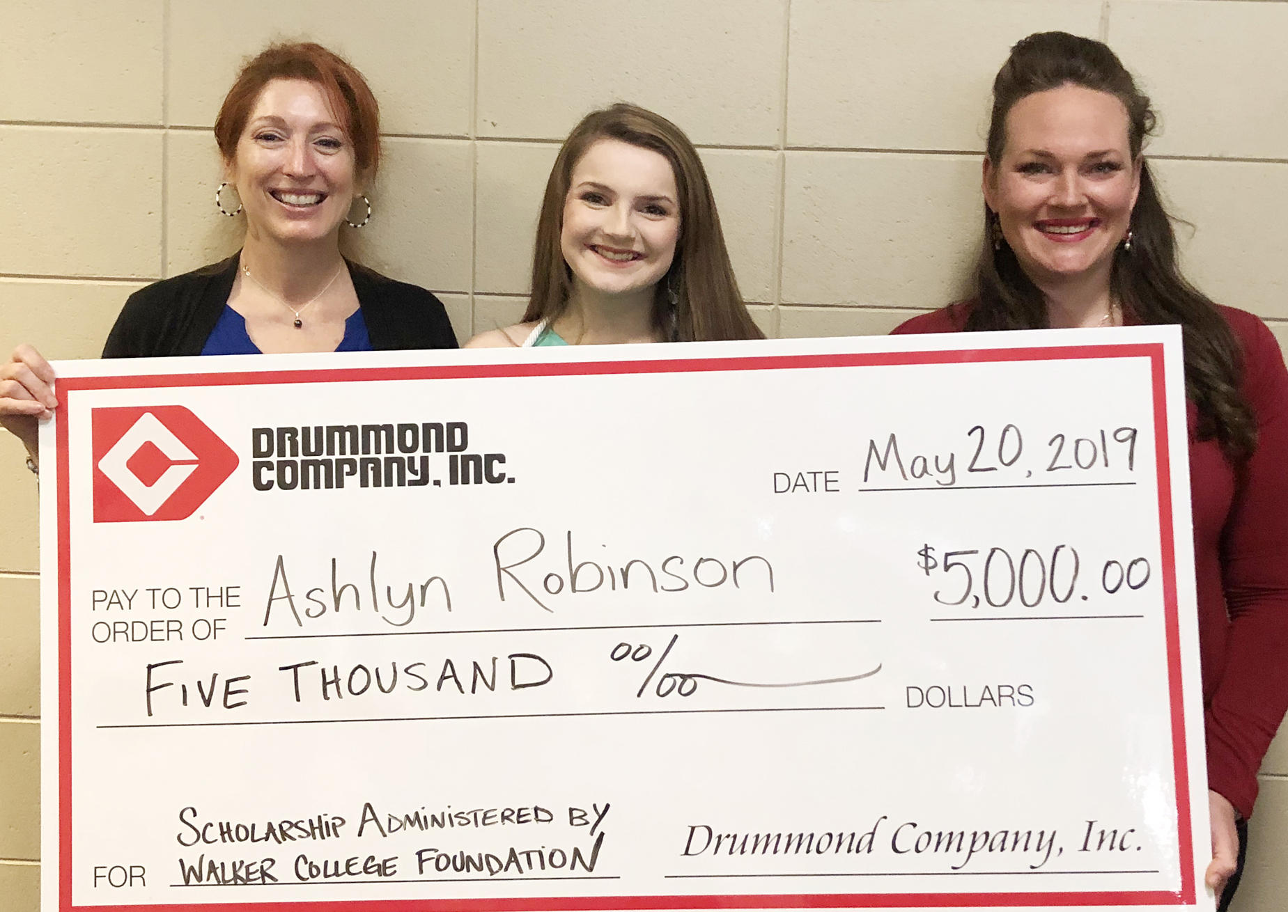 Ashlyn Robinson (ctr) is awarded the Drummond Company scholarship by Holly and Krystal at the Pinson Valley High School senior honors program.
