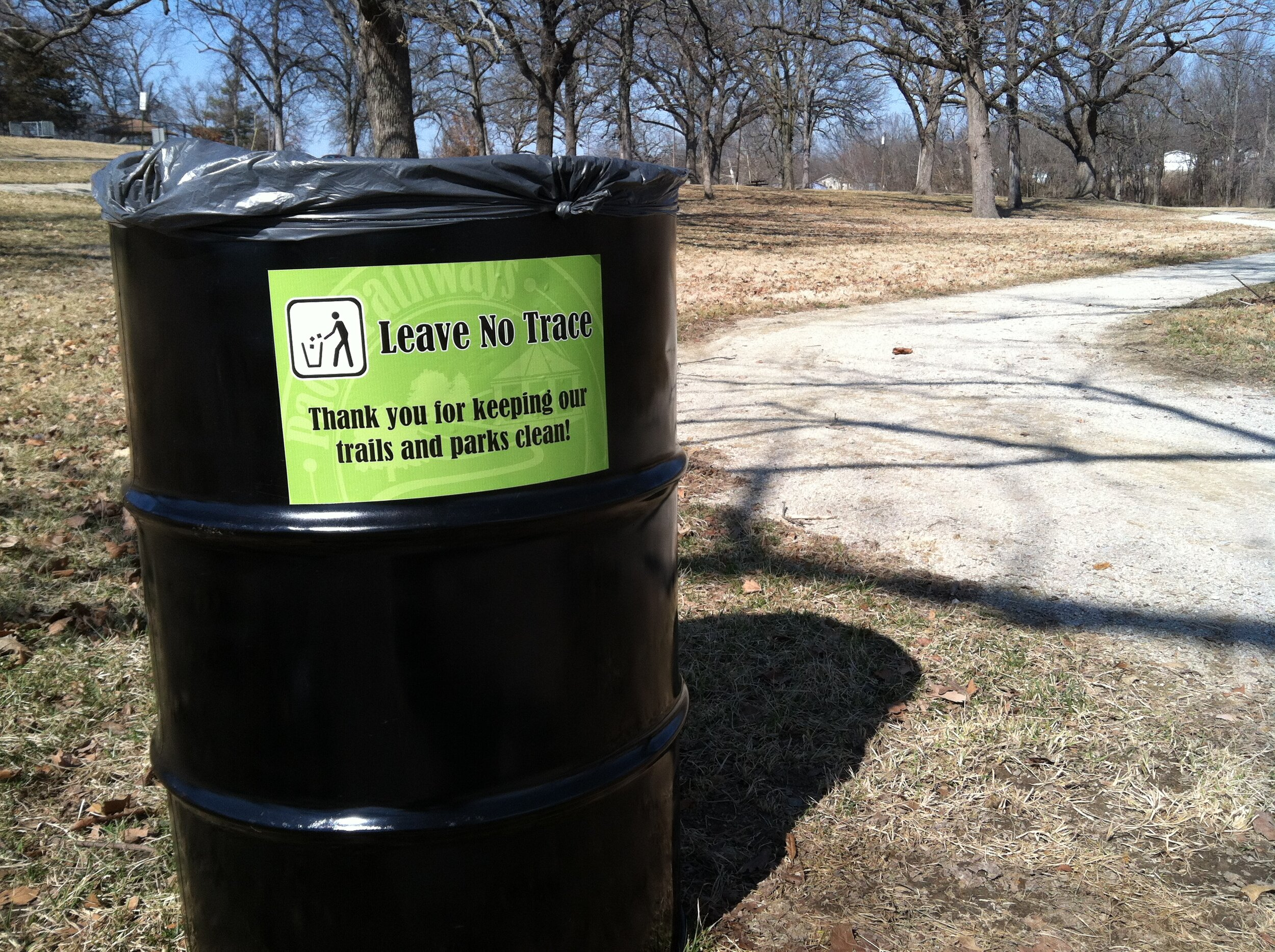 Adhesive labels attached to additional trash bins along trails