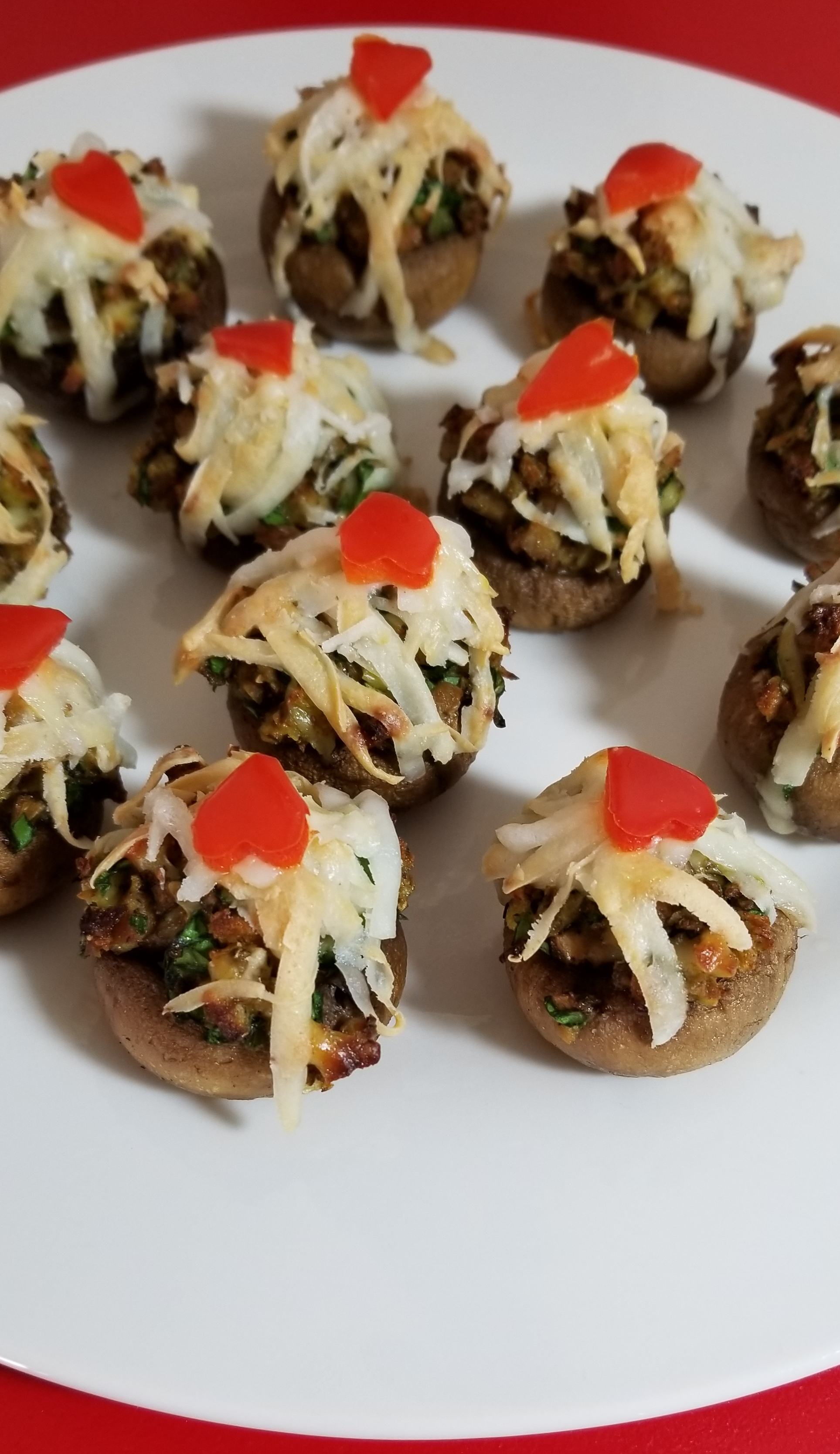 Simple stuffed mushrooms with chicken apple sausage, spinach, almond cheese, and a tiny red pepper heart to top them off!