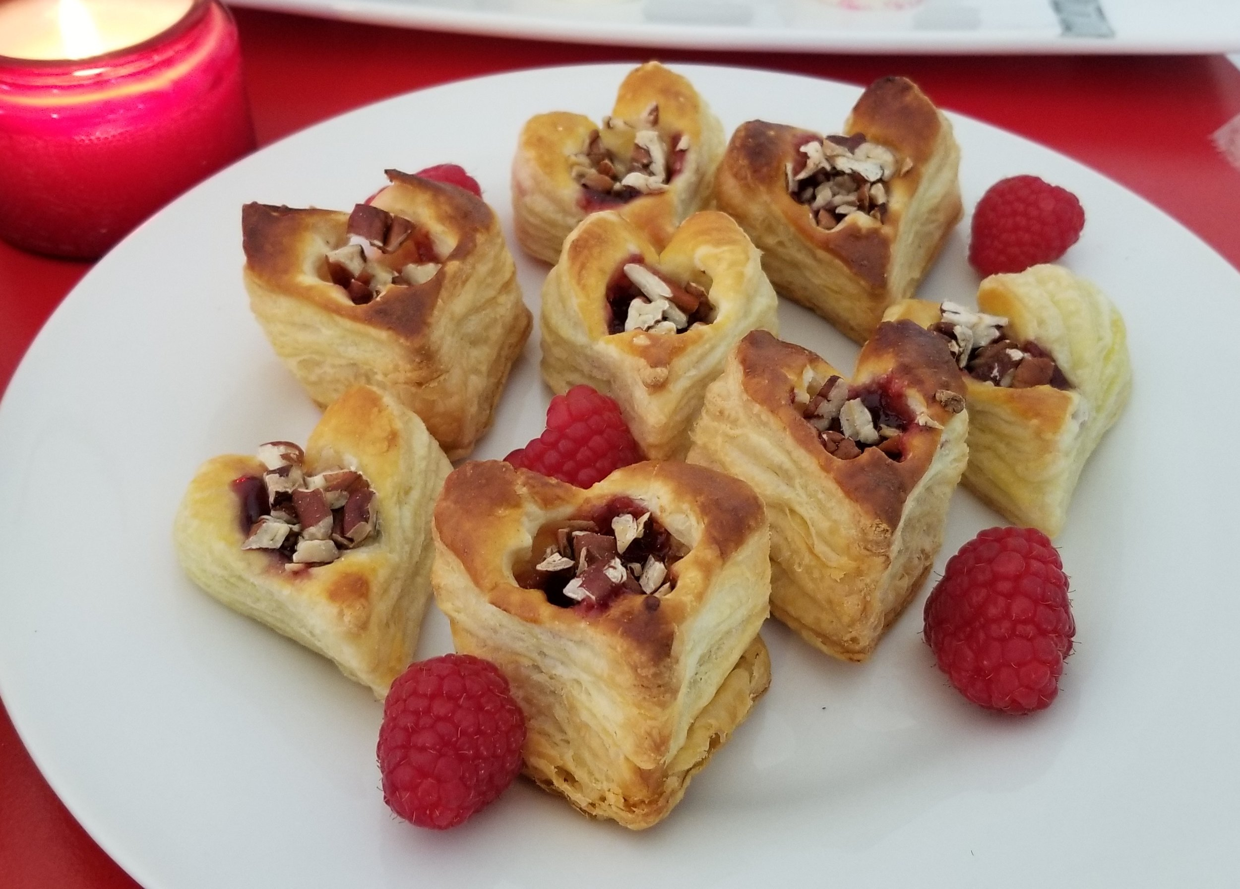 Brie and raspberry puffs made with puff pastry, brie, raspberry jam and toasted pecans.