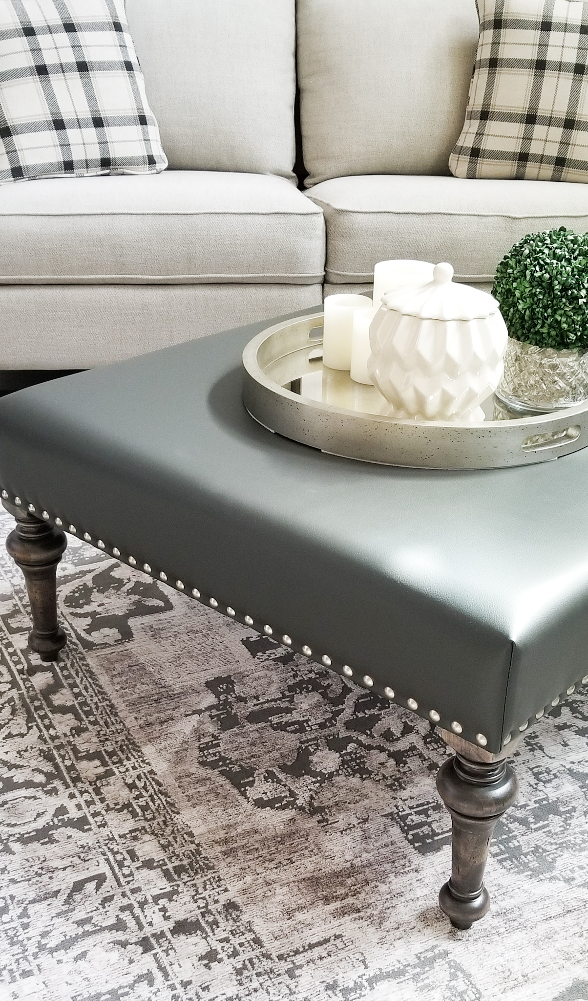 Turned leg ottoman in gray leather.