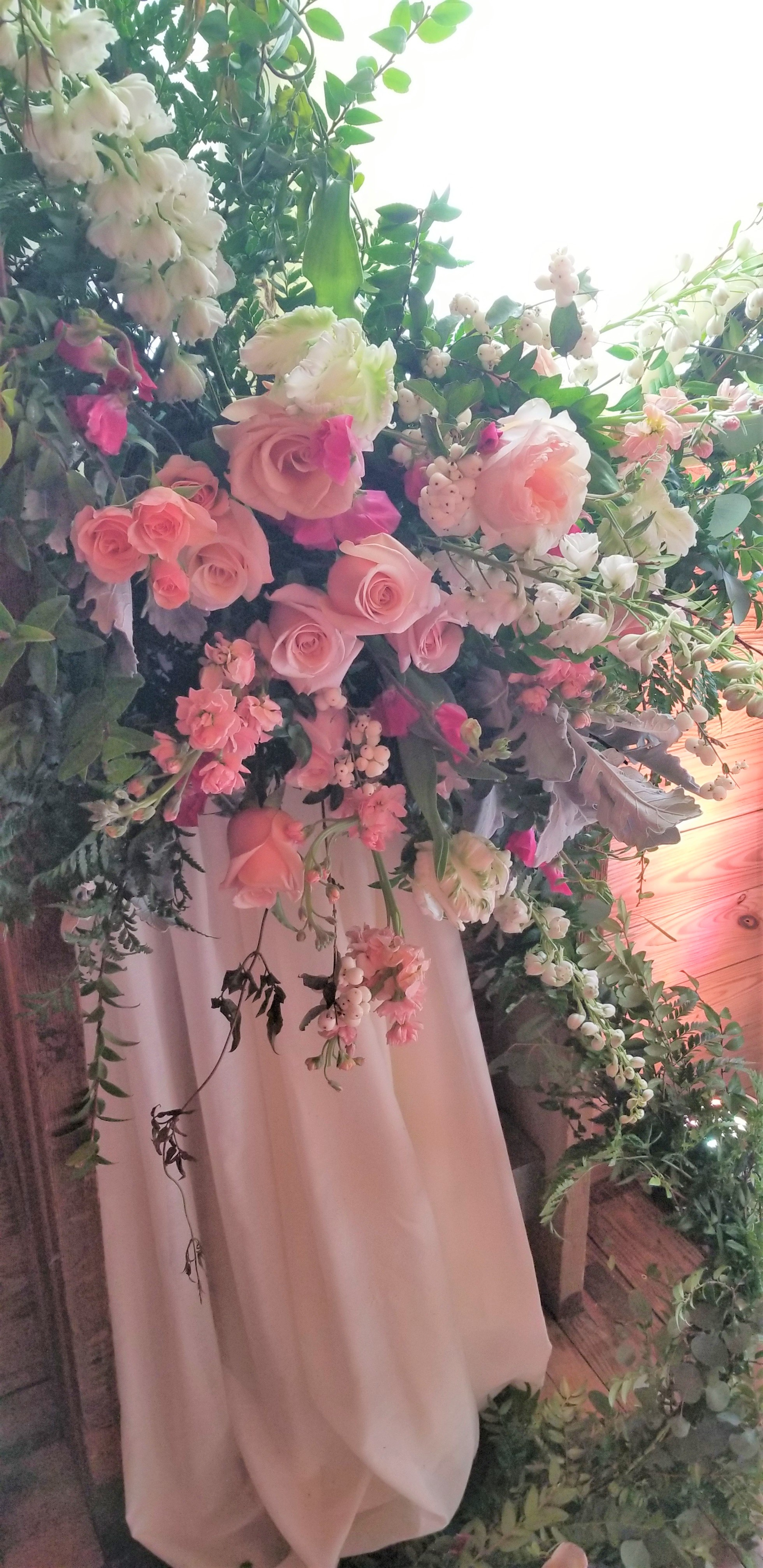 Floral tie-backs with white linen drapes and lush vines.