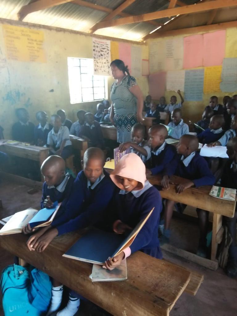 Nampaso of IndiMark Kenya distributes the donated books to the Makindu primary school.