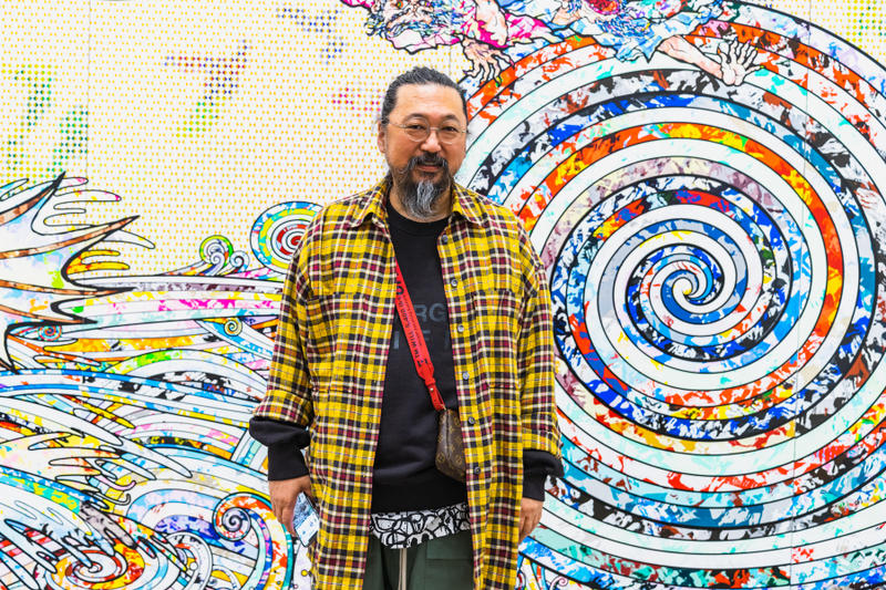 """One of the most acclaimed artists to emerge from postwar Asia, Takashi Murakami—""""the Warhol of Japan""""—is known for his contemporary Pop synthesis of fine art and popular culture, particularly his use of a boldly graphic and colorful anime and manga cartoon style. Murakami became famous in the 1990s for his """"Superflat"""" theory and for organizing the paradigmatic exhibition of that title, which linked the origins of contemporary Japanese visual culture to historical Japanese art. His output includes paintings, sculptures, drawings, animations, and collaborations with brands such as Louis Vuitton. """"Japanese people accept that art and commerce will be blended; and in fact, they are surprised by the rigid and pretentious Western hierarchy of """"high art',"""" Murakami says. """"In the West, it certainly is dangerous to blend the two because people will throw all sorts of stones. But that's okay—I'm ready with my hard hat."""""""
