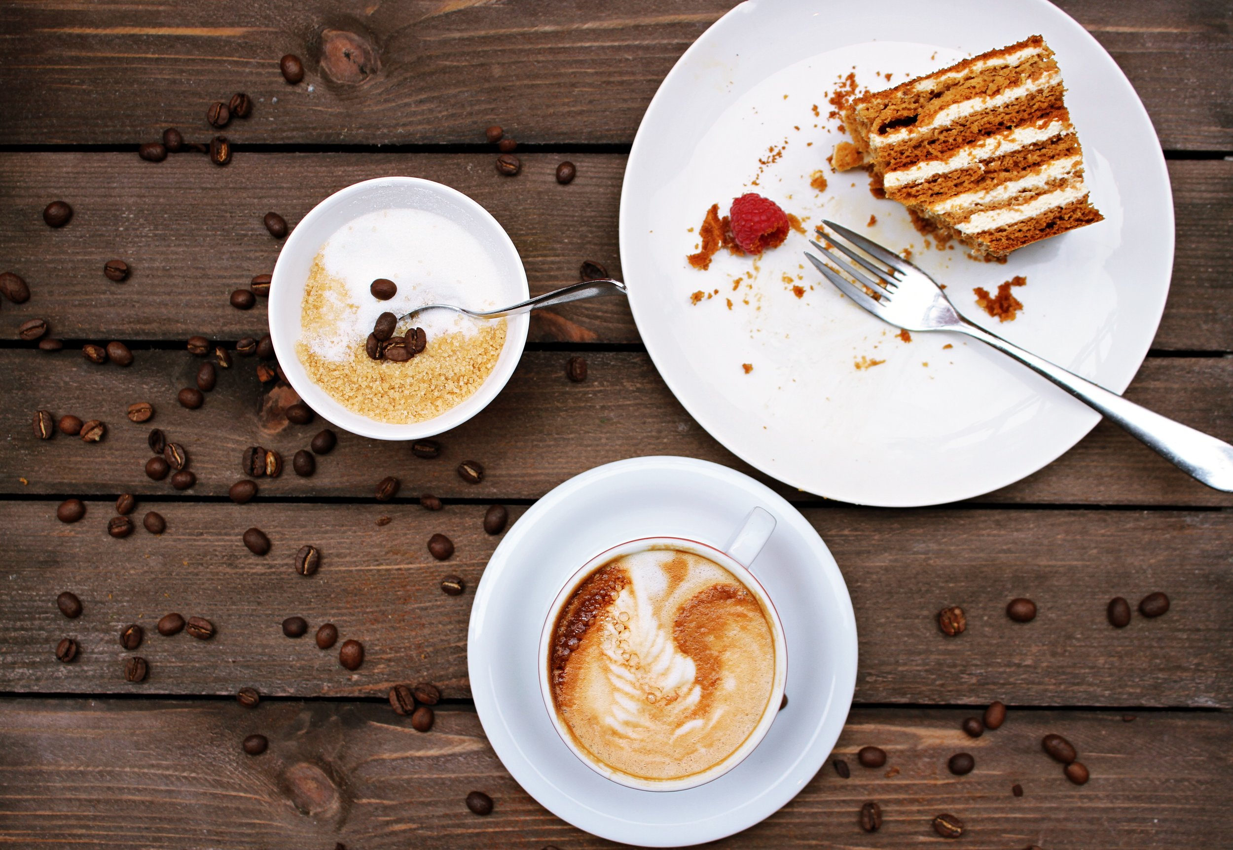 Image: half eaten cake and spoon positioned to side with sugar bowl and latte on table