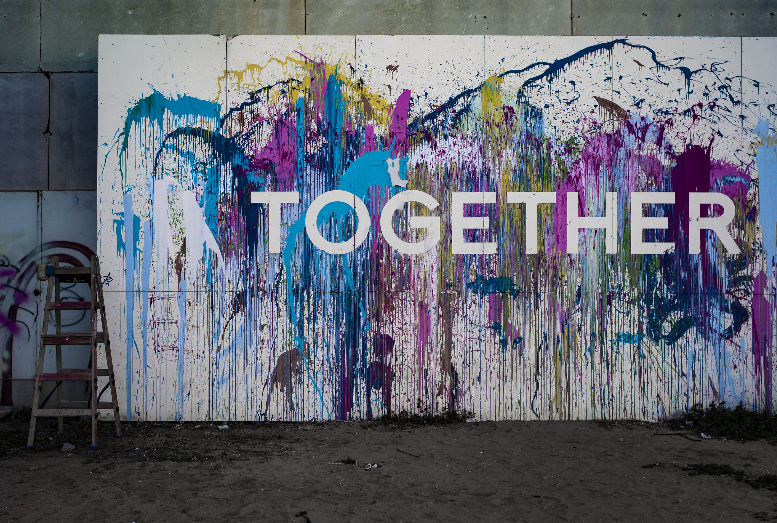 Image: Paint splattered wall with the word 'Together' written across.