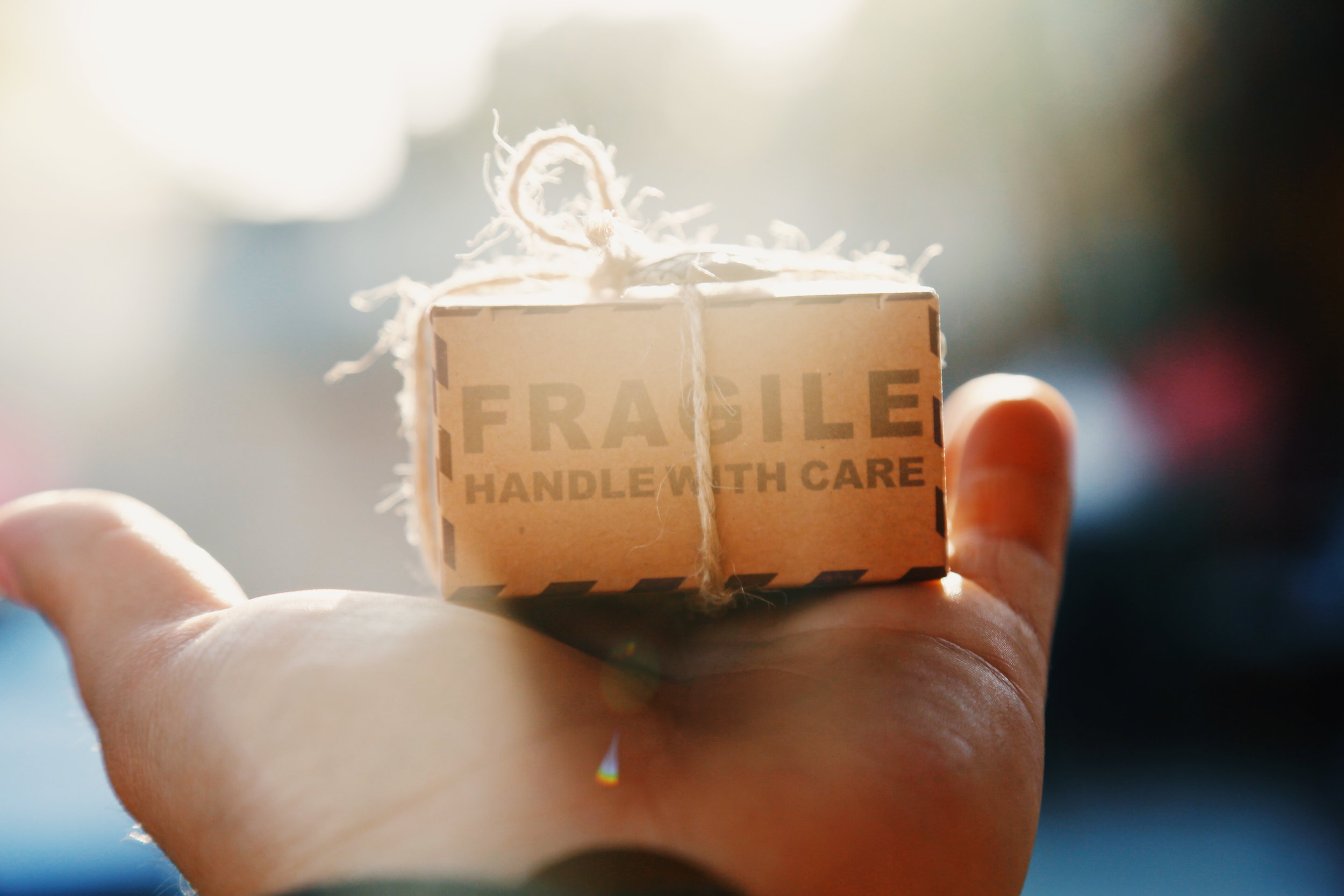 Image shows a hand with a small brown box that reads 'fragile - handle with care' to highlight the care and commitment Hygge Me places on providing beautifully packaged items.