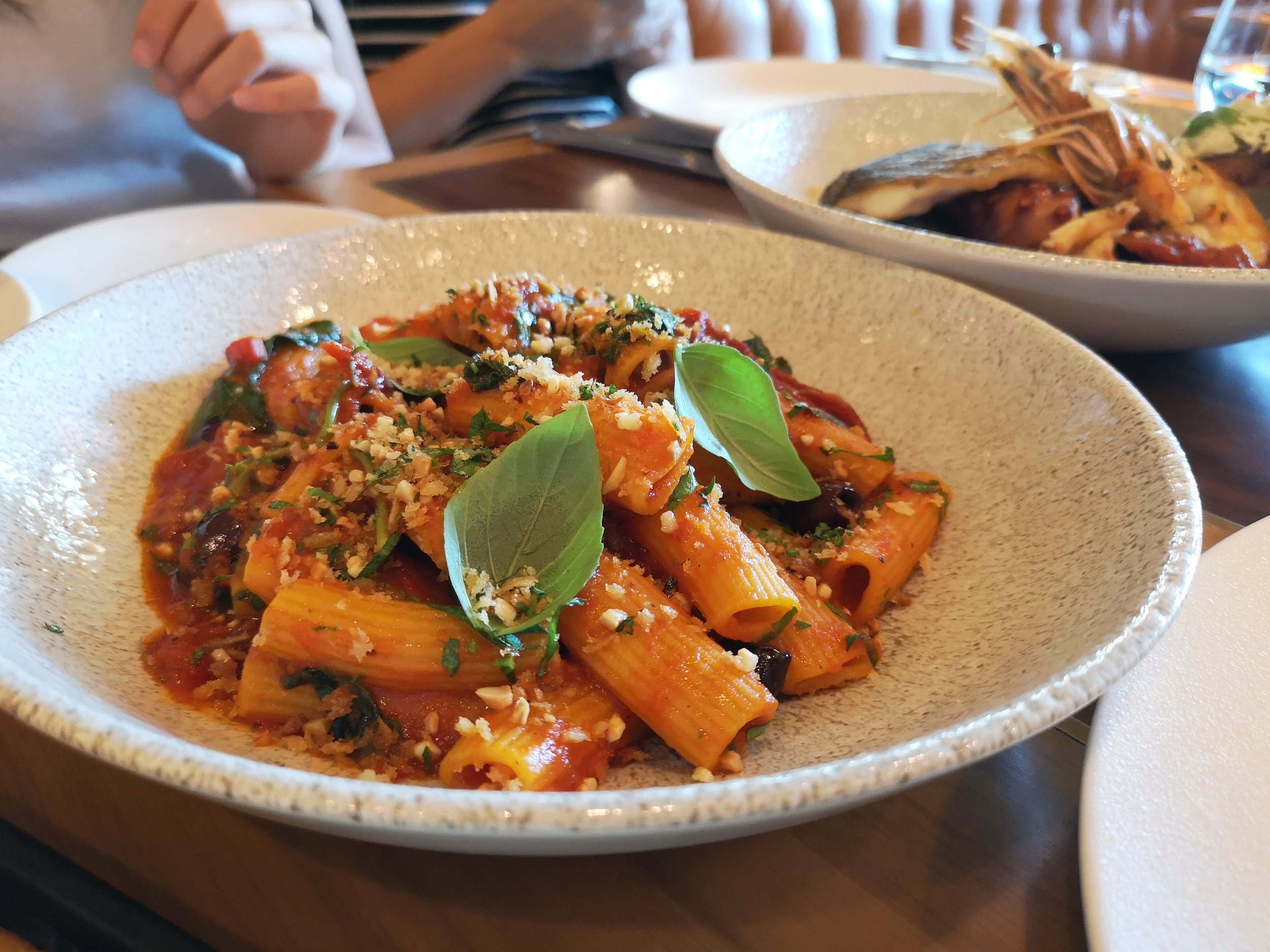 Rigatoni with spicy tomato sauce, taggiasche olives, bitter greens, toasted almonds (AED105)