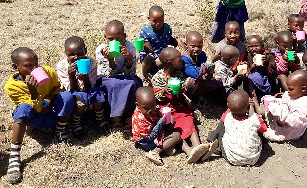 Children at the Olmoti clinic eat breakfast.