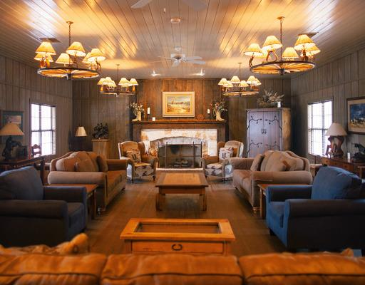 Chisholm Trail Meeting Room - This meeting space is designed and furnished with rustic elegance. It is one of the most comfortable spaces on property. It has a large stone fireplace, beautiful reclaimed hardwood floors, a complete kitchen, and comfortable seating for a relaxed informal meeting.[Accommodates 25-30 people]